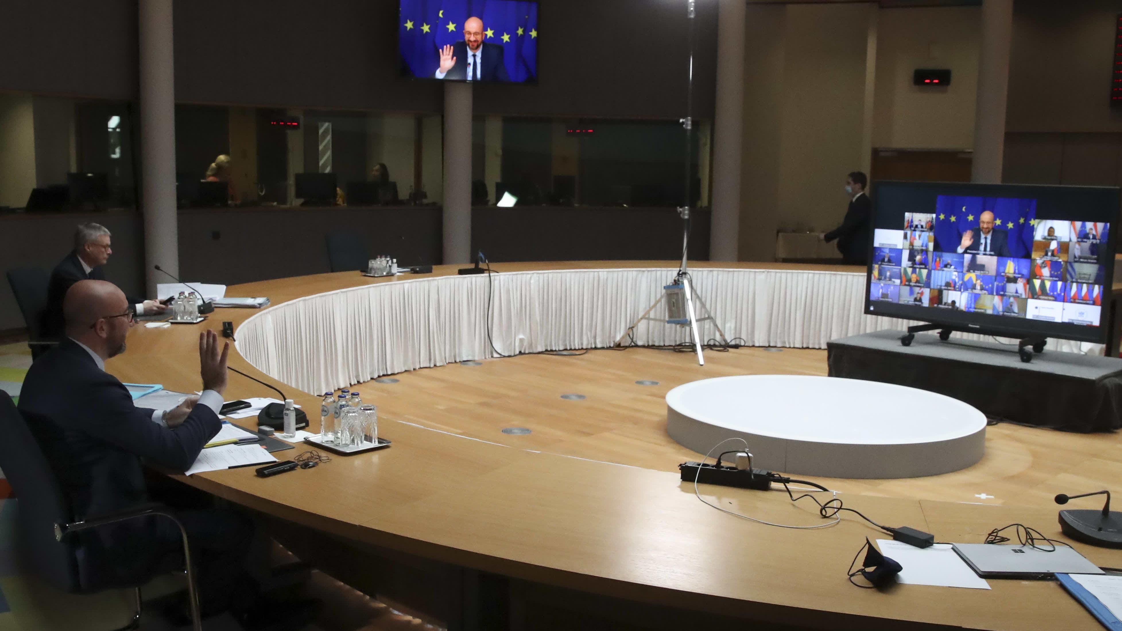 Charles Michel heiluttaa kättään näytöllä näkyville EU-maiden johtajille