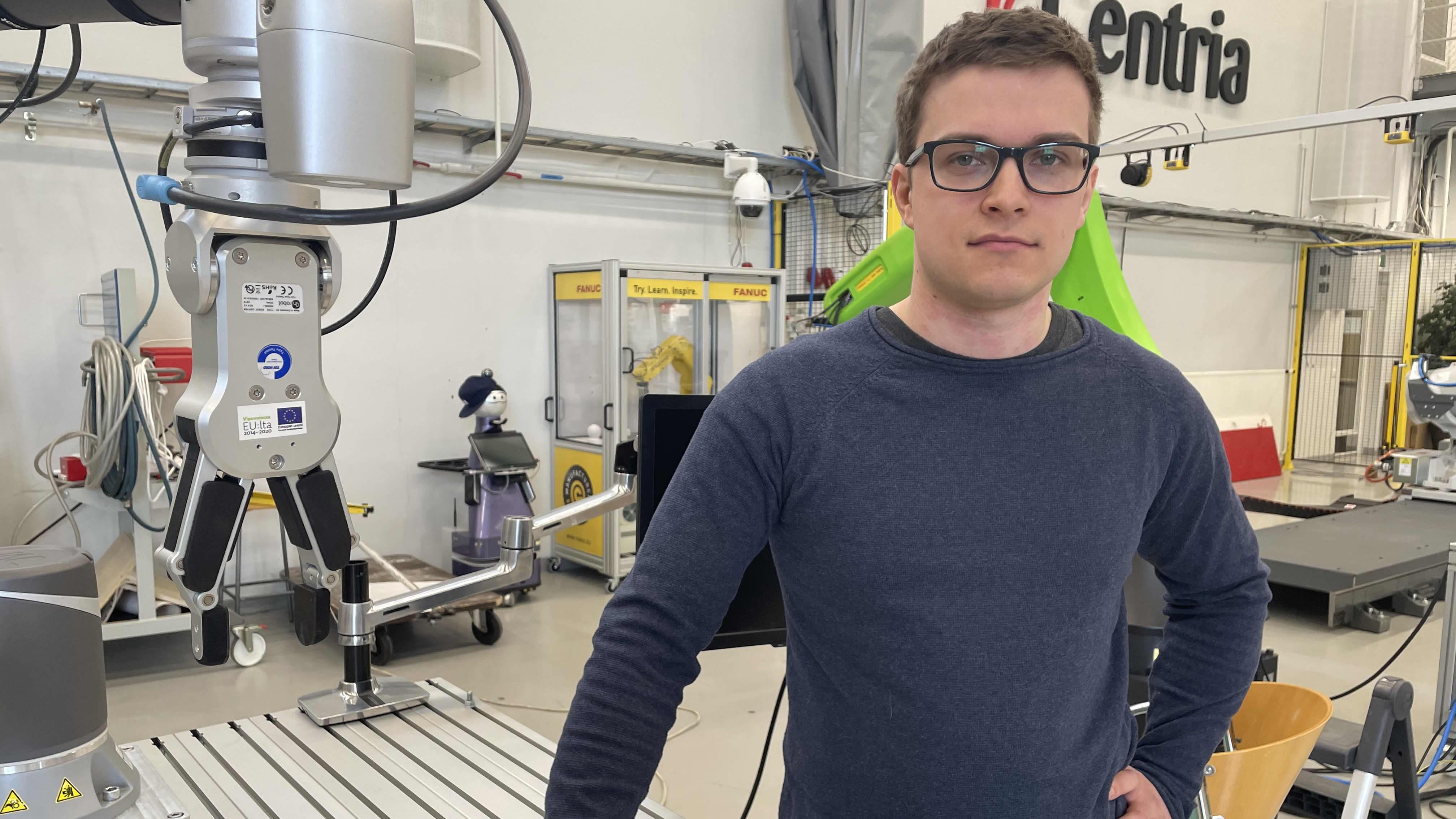 Ylivieskalainen Juho Valkola seisoo Centria-ammattikorkeakoulun robottilabissa laitteiden vieressä.