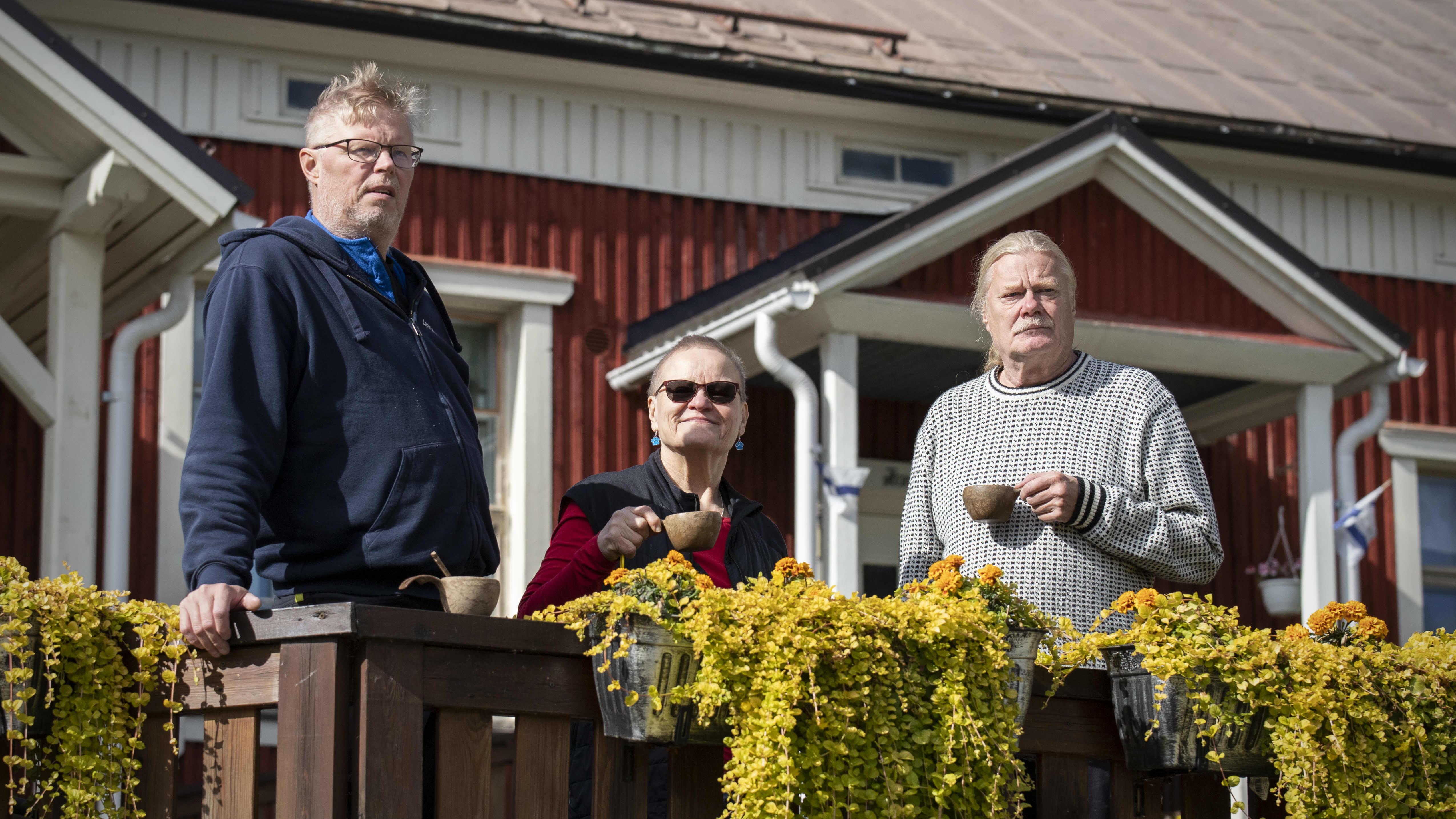 Jorma Kuiri, Sisko Väisänen ja Kari Lintula juovat kahvia Möhkön majatalon edessä.