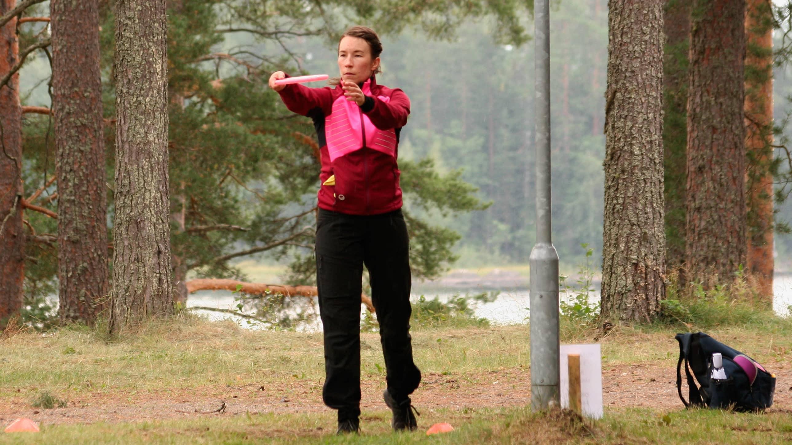 Katri Koponen seisoo frisbee ojennetuissa käsissään frisbeegolfradalla ja valmistautuu heittämään, taustalla mäntymetsää ja lampi.