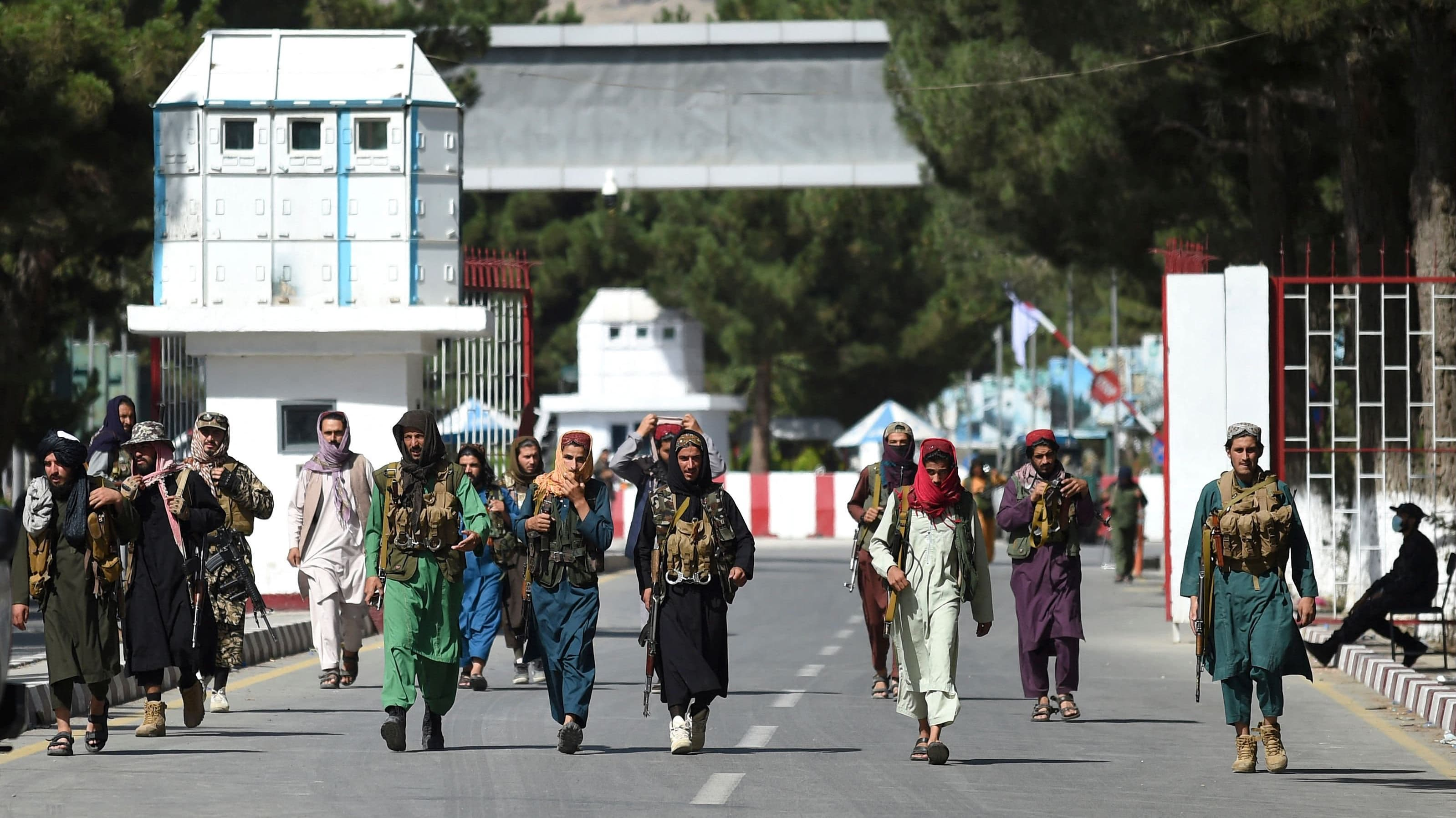 Talibankrigare promenerar vid huvudingången till Kabuls flygplats.