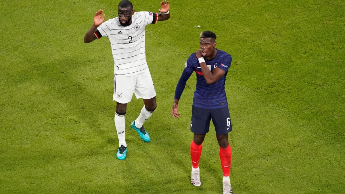 Antonio Rüdiger levittelee käsiään, Paul Pogba pitelee selkäänsä.