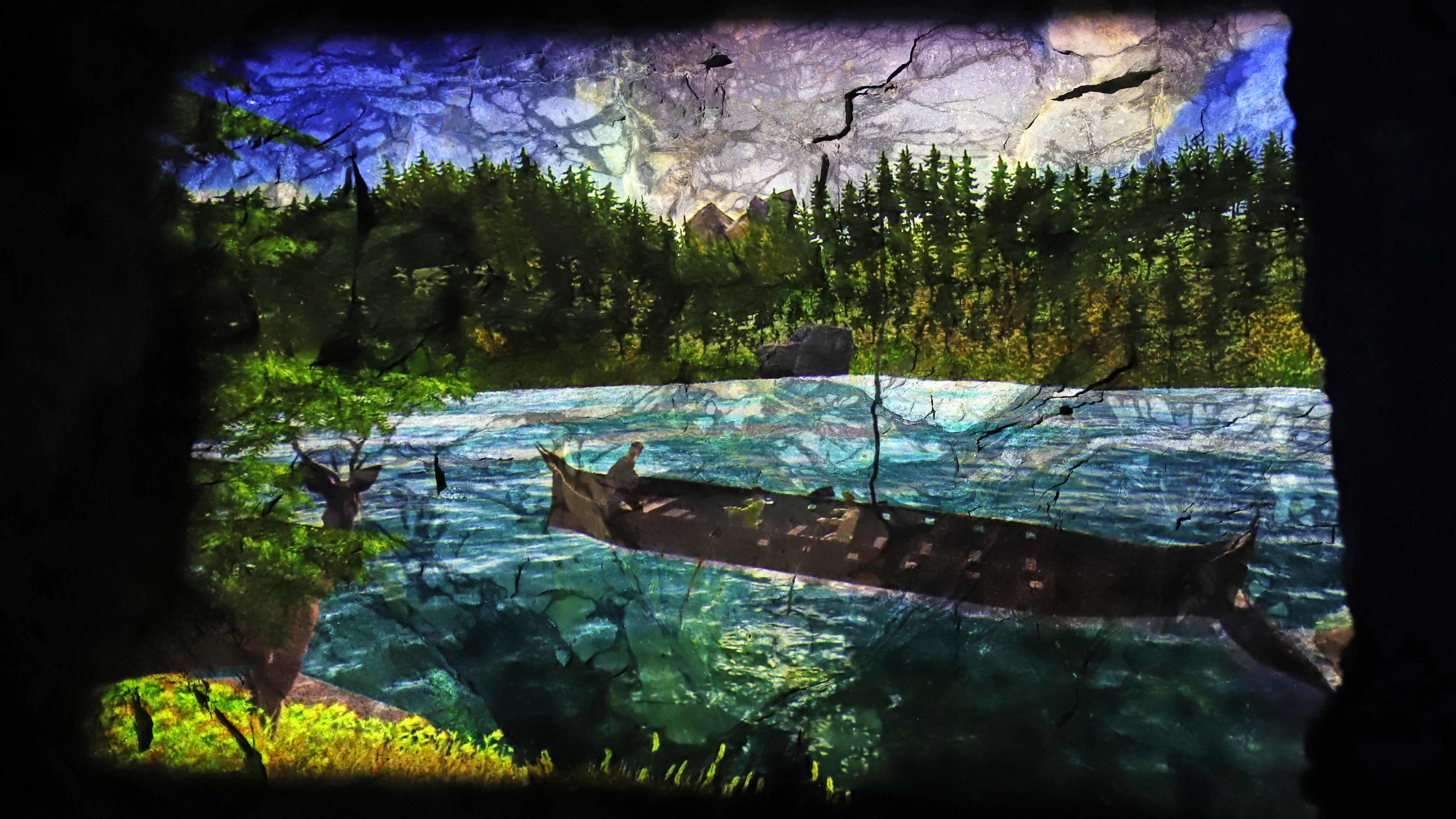 Kalevala-aiheinen videoteos Saimaan Taideluola Retretin luolan seinässä.
