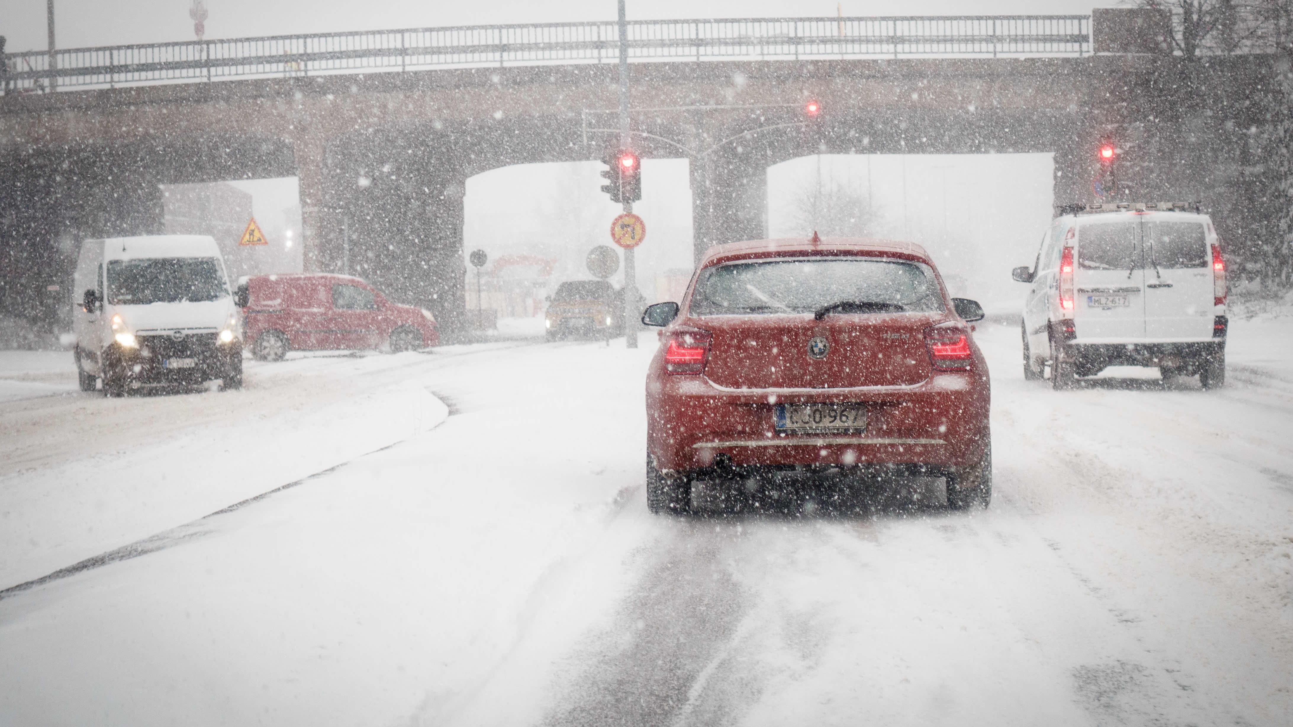 Henkilöautoja liikenteessä lumipyryssä.