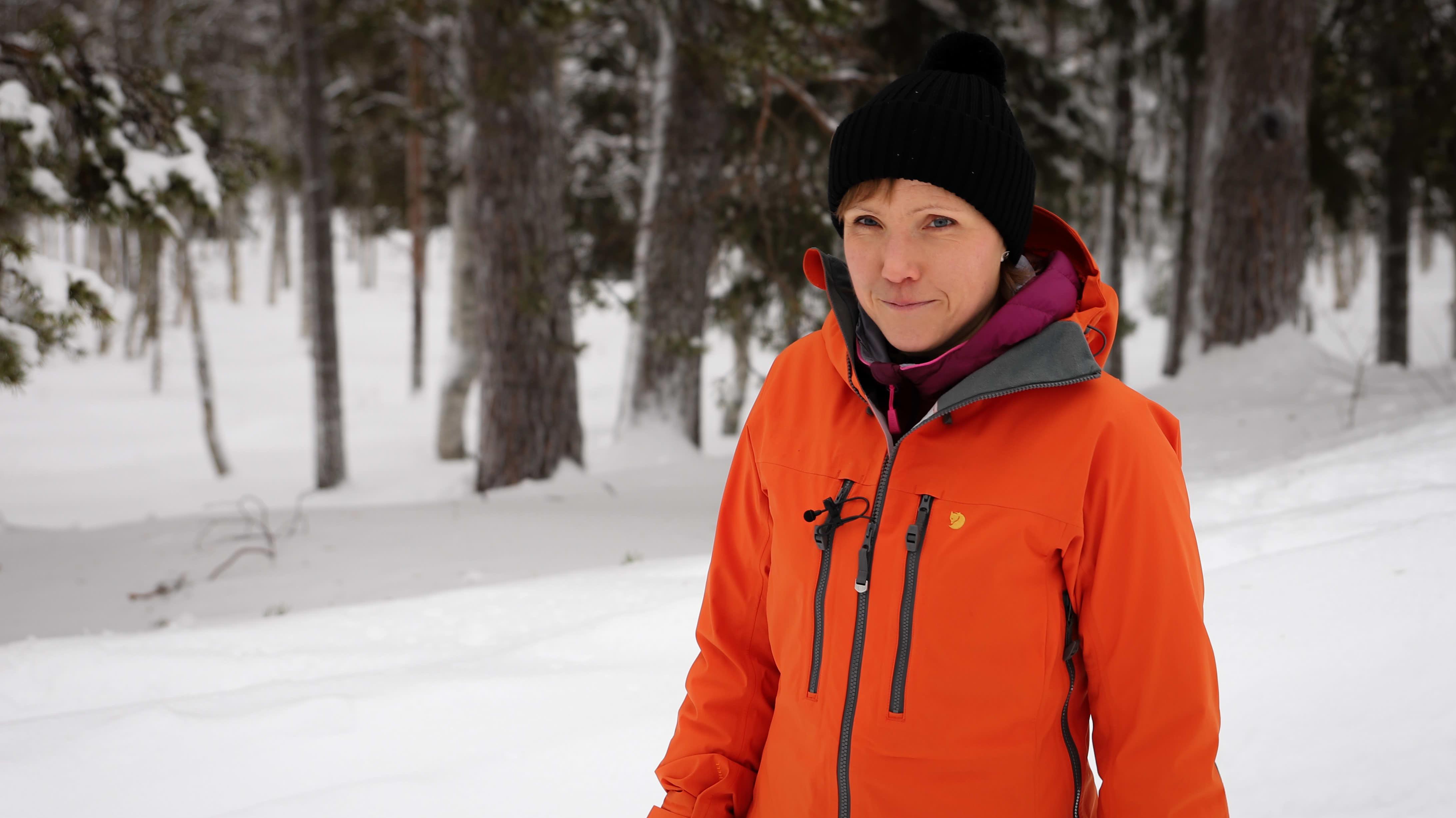 Kaisa Sali lumisessa maisemassa. Taustalla on havumetsää. Kaisalla on punainen kuoritakki ja musta pipo. TV-haastattelussa käytetty nappimikrofoni johtoineen pilkistää takin rintataskusta.