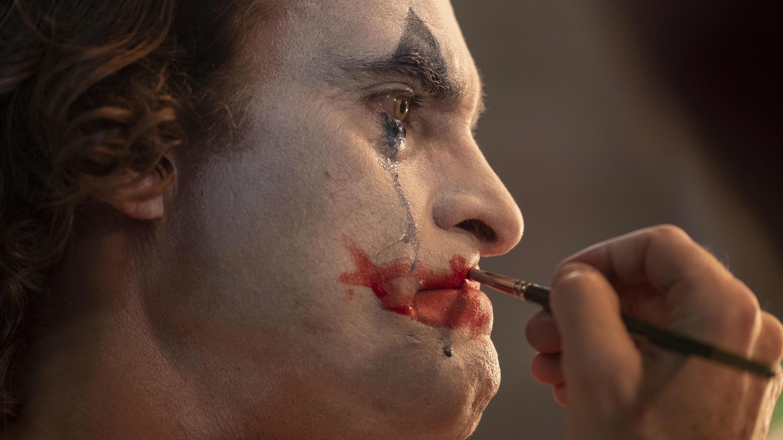 Närbild då Arthur (Joaquin Phoenix) sminkar sig till clown samtidigt som han gråter och blå mascara rinner nerför kinden.