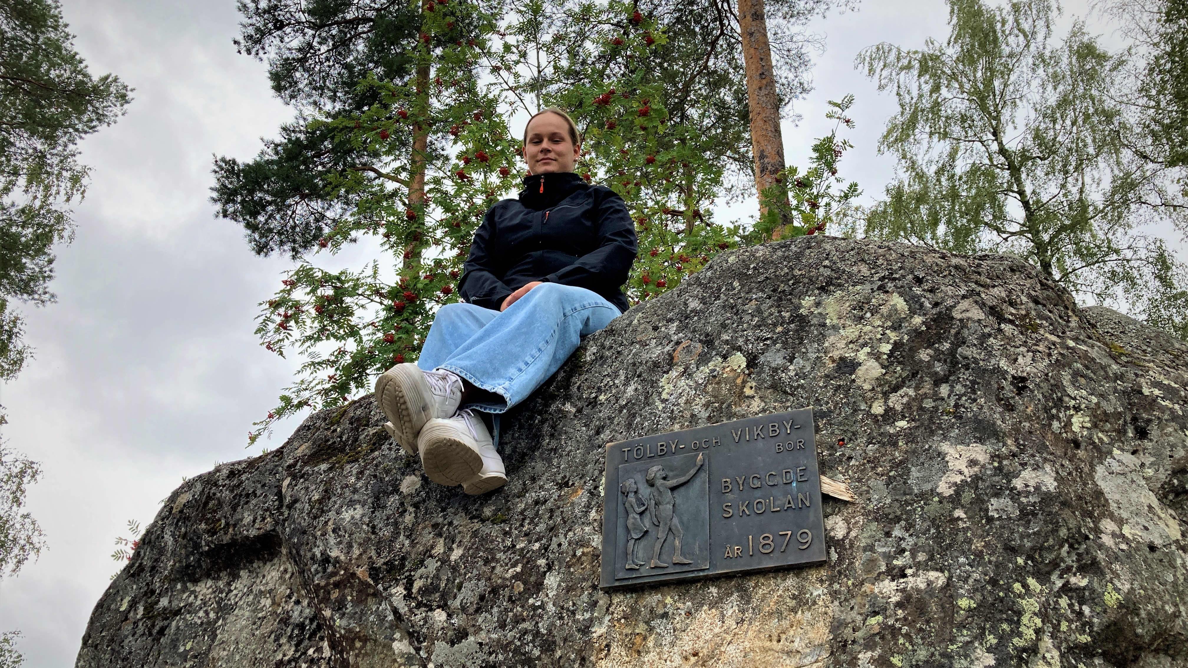 Mustasaarelainen Paula Jaskari istuu ison kiven päällä vanhan kyläkoulunsa pihalla.