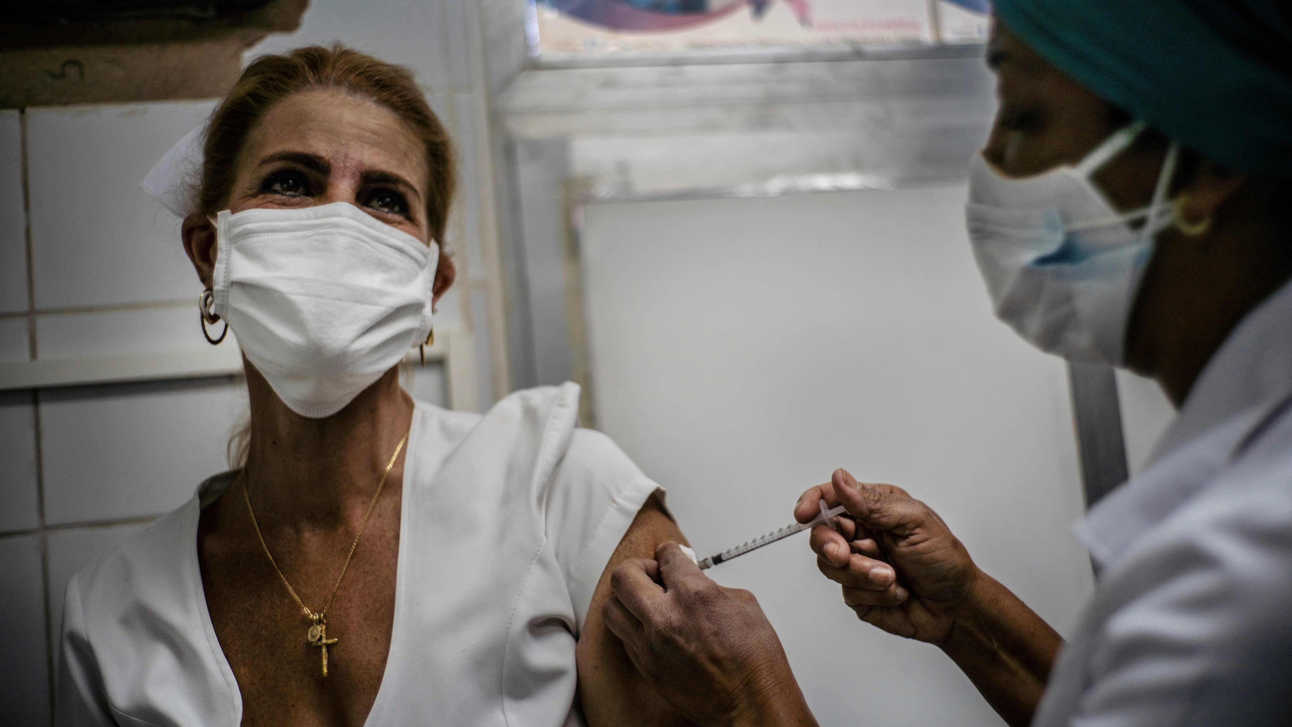 Sairaanhoitaja pistää koronavirusrokotteen terveystyöntekijän käsivarteen. Molemmilla on kasvomaskit. Huoneessa on valkoiset seinät.