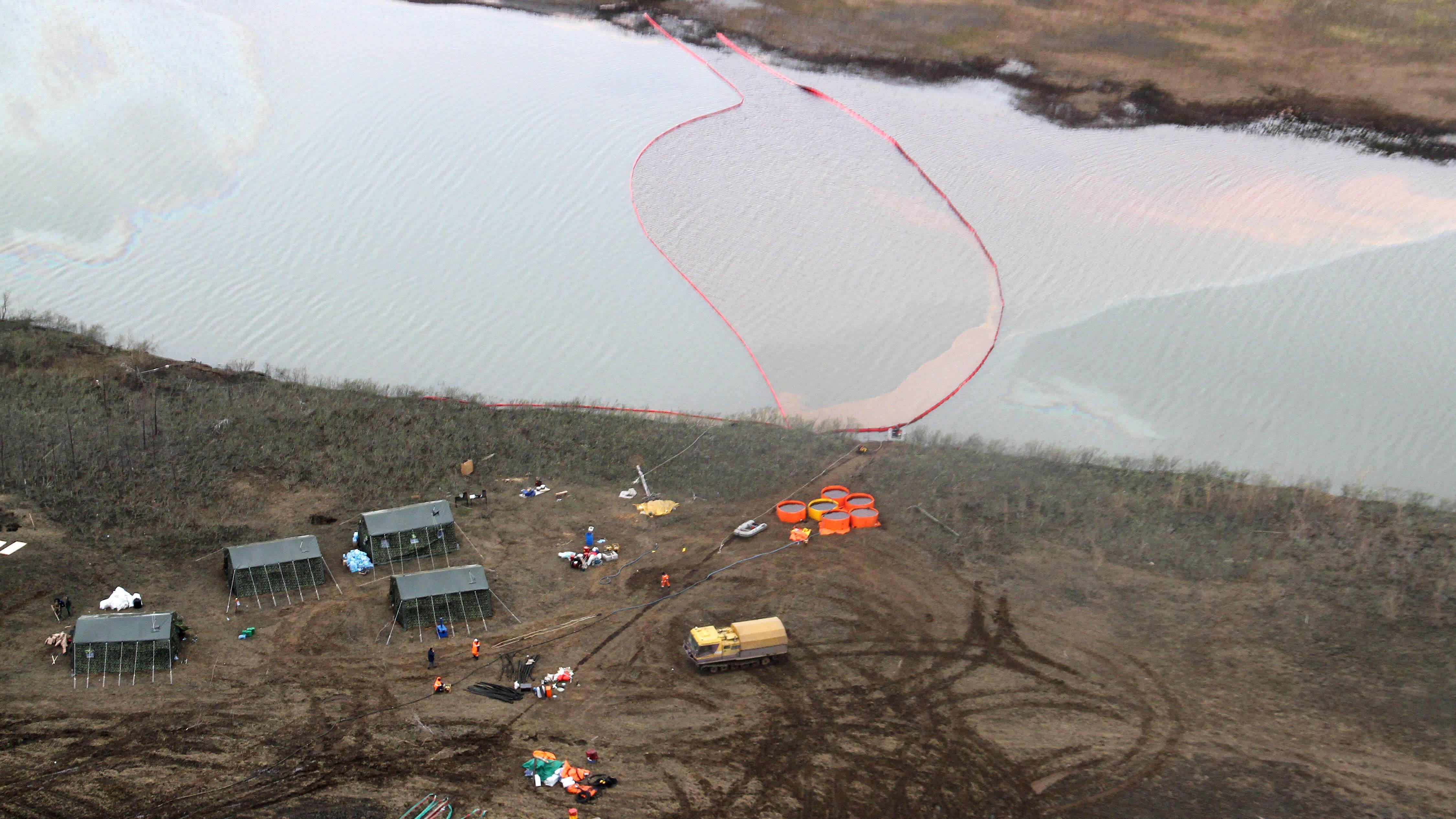 Puomeilla rajattu öljyvuoto joessa ilmasta kuvattuna.