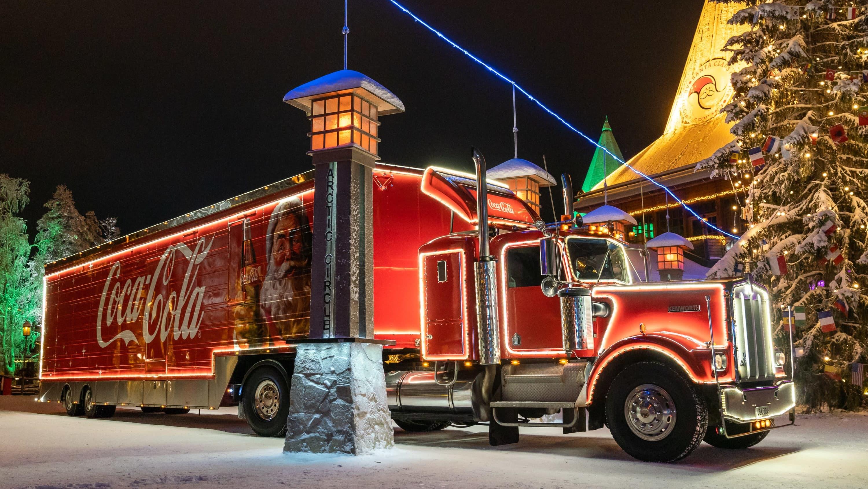 Coco-Colan valaistu joulurekka pysäköitynä Rovaniemellä joulupukin pajan edessä.