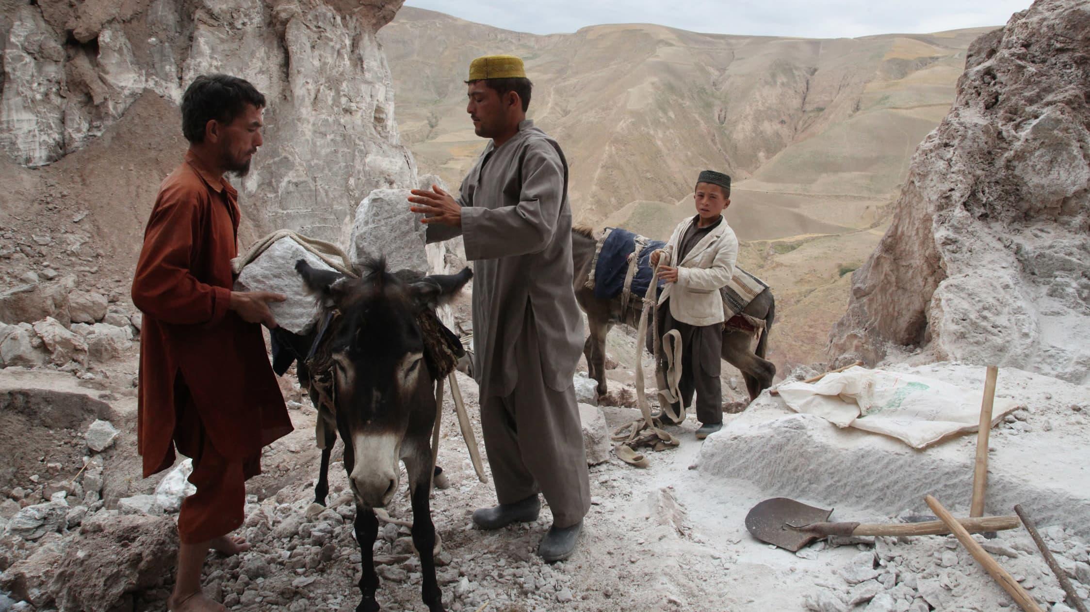Afganistanilaiset miehet kiinnittävät suolakiviä aasin selkään.