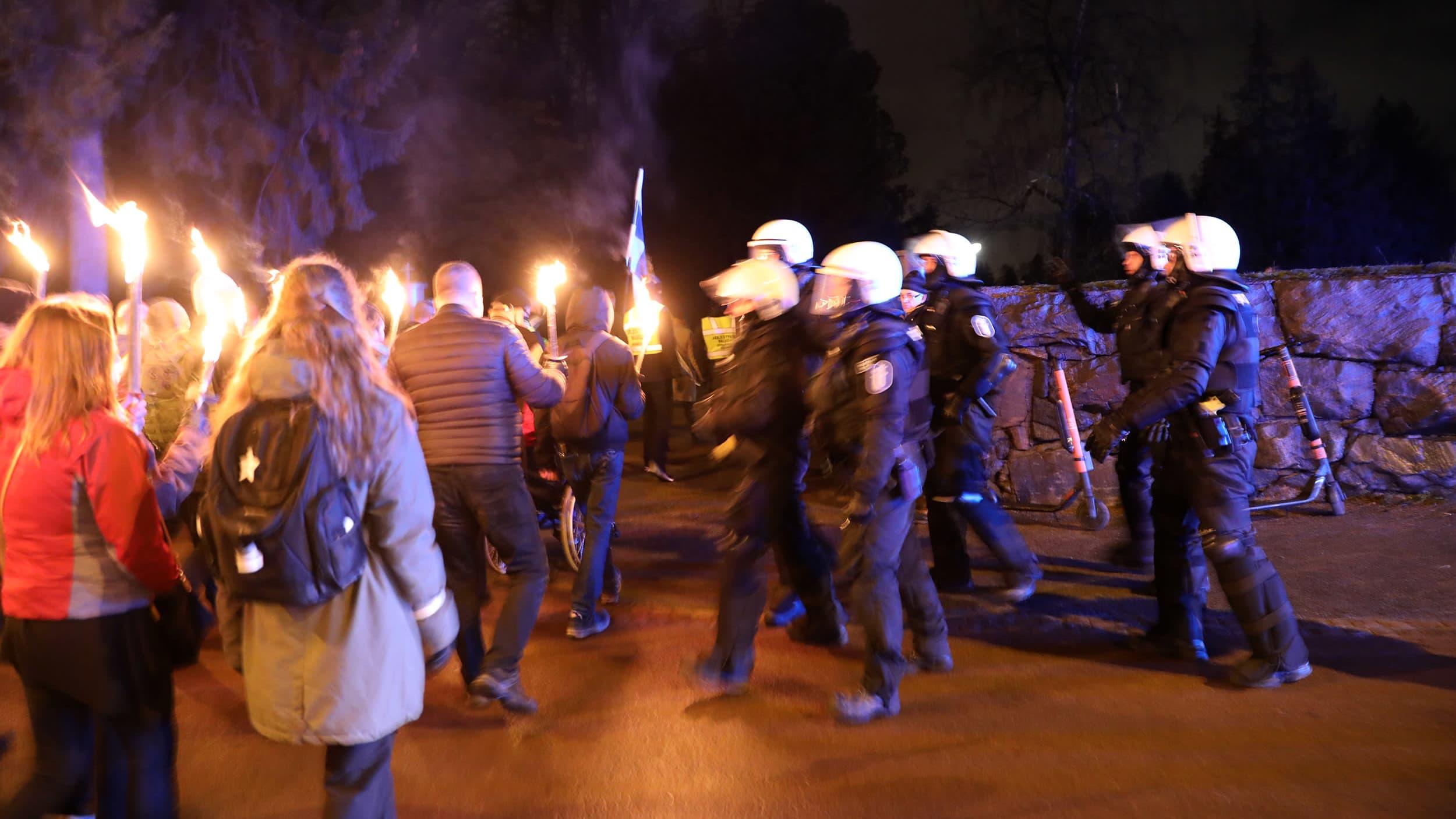 ihmisiä marssilla soihtujen kanssa, joukko mellakkapoliiseja vierellään