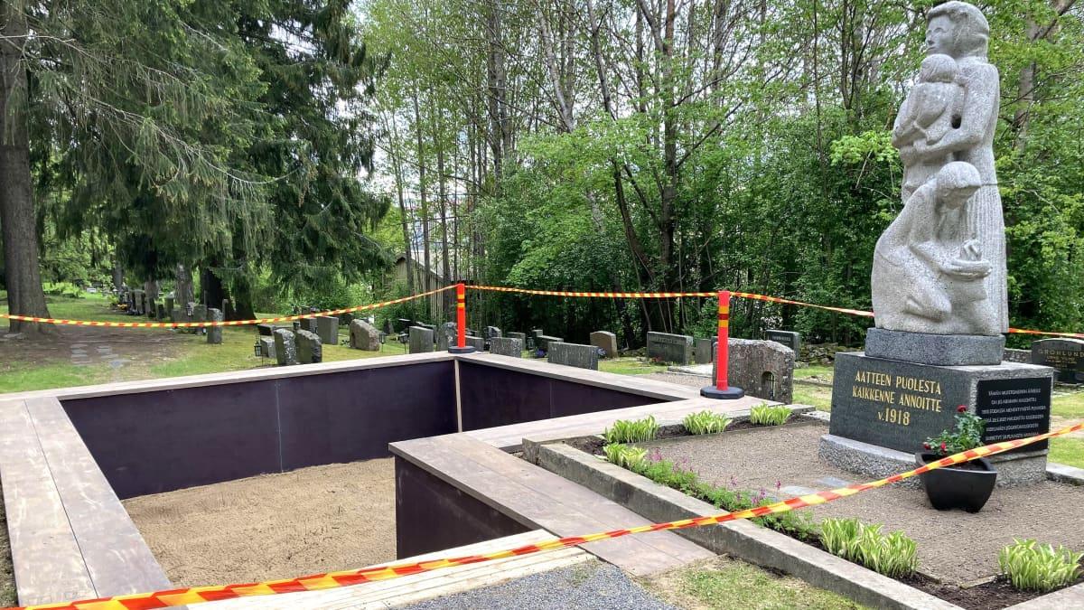 Tyhjä hauta, jonka vieressä sisällisodan muistomerkki Heinolan keskustan hautausmaalla.