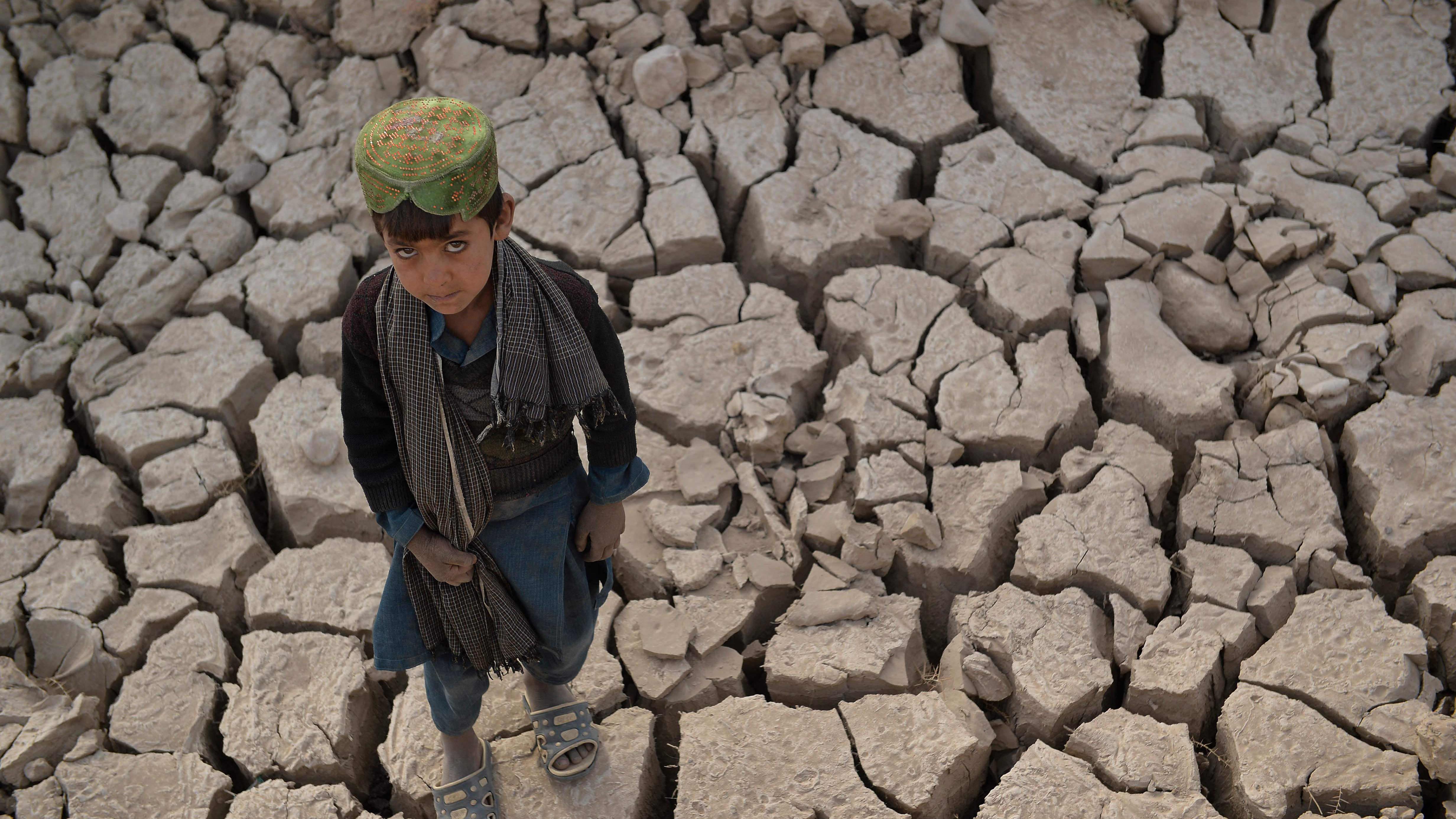 Pieni poika seisoo kuivuneella pellolla ja katsoo kameraan.