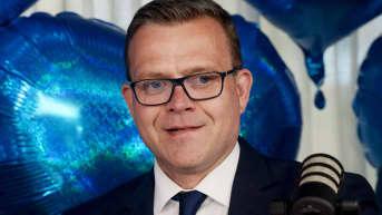 Petteri Orpo, en man i kostym och glasögon framför en mikrofon.