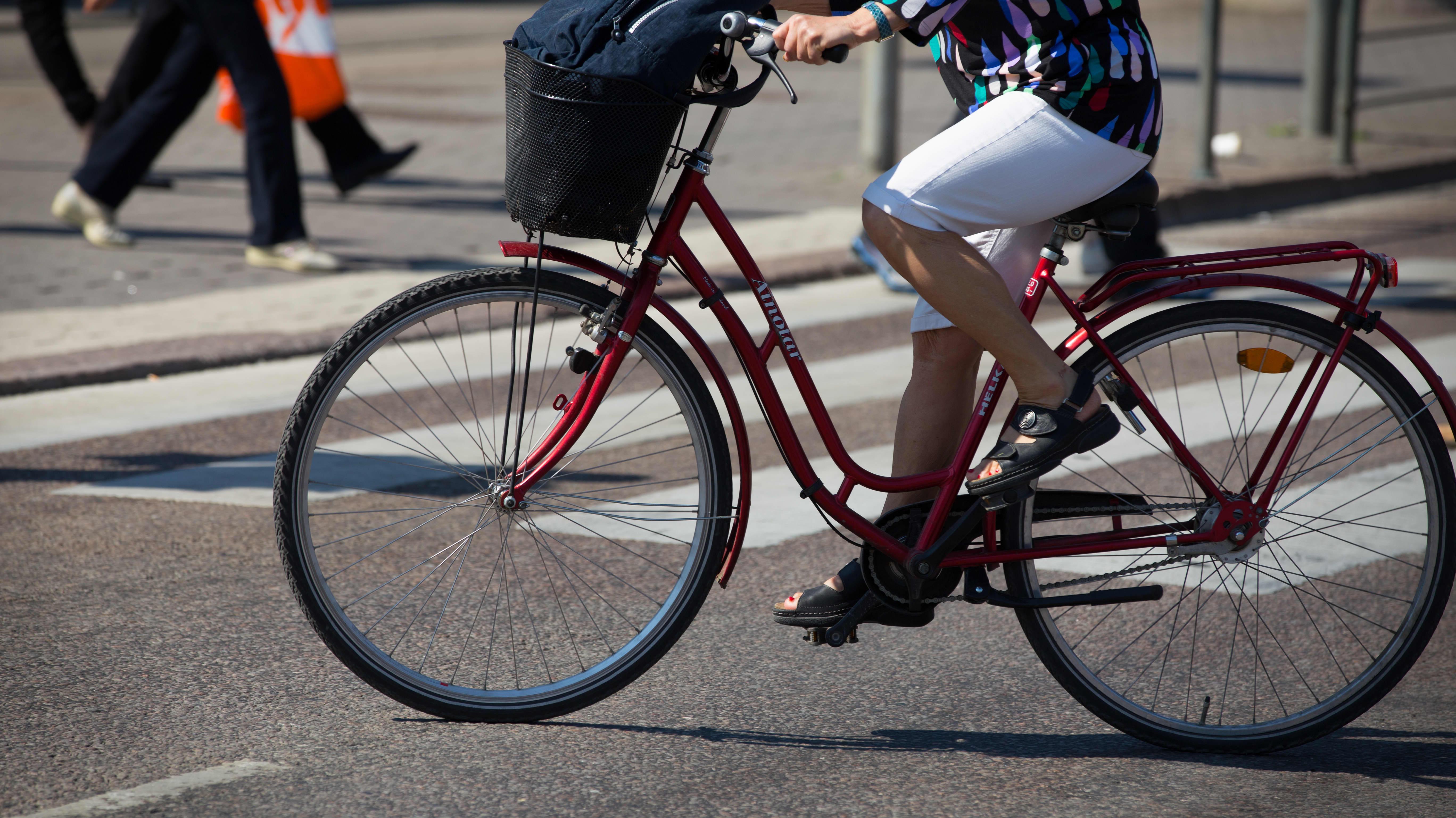 Anonyymi nainen polkee pyörällä kaupungissa kesällä.
