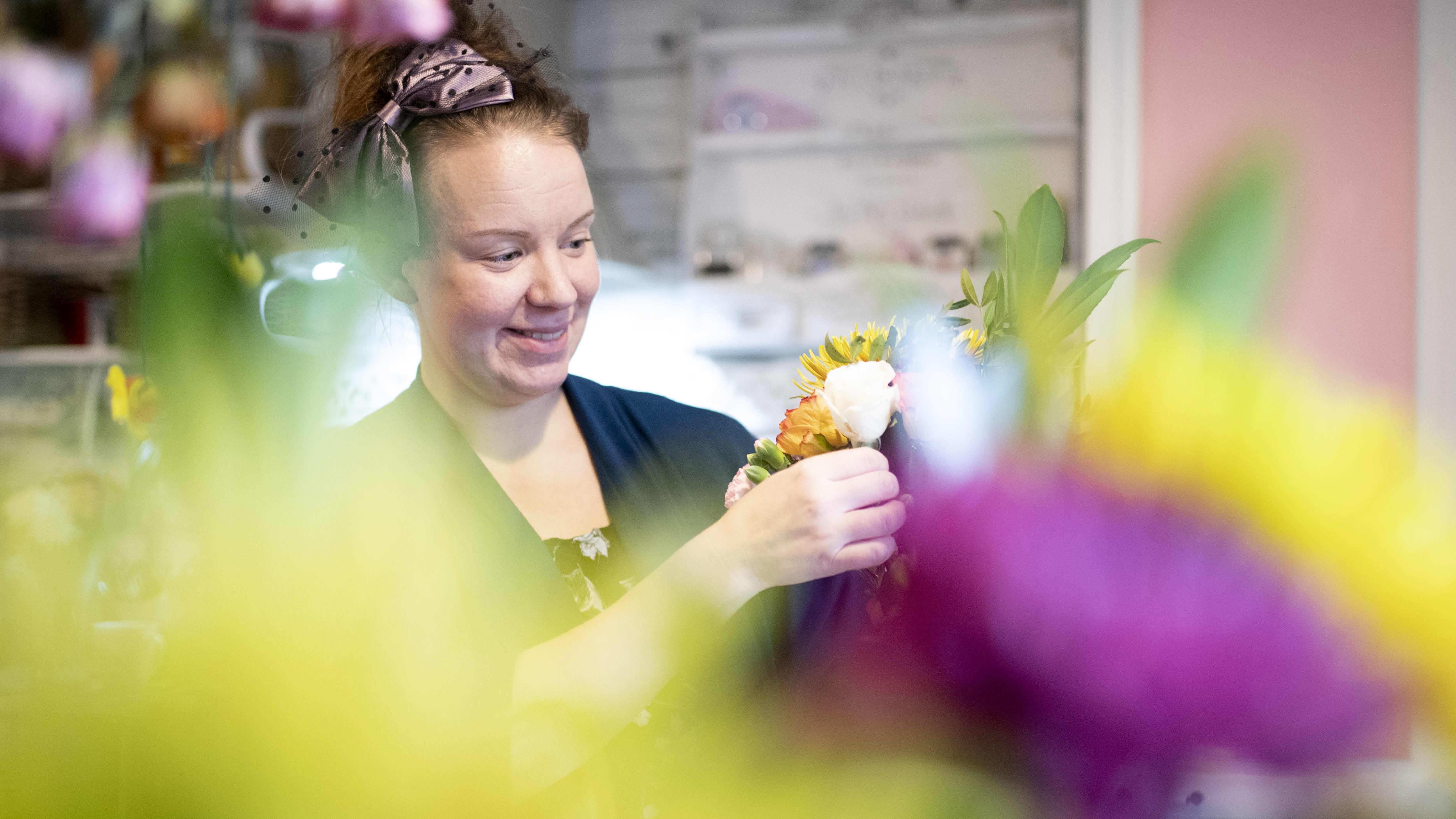 Kukkien välistä kuvattu nainen, joka sitoo kukkakimppua keittiössään.