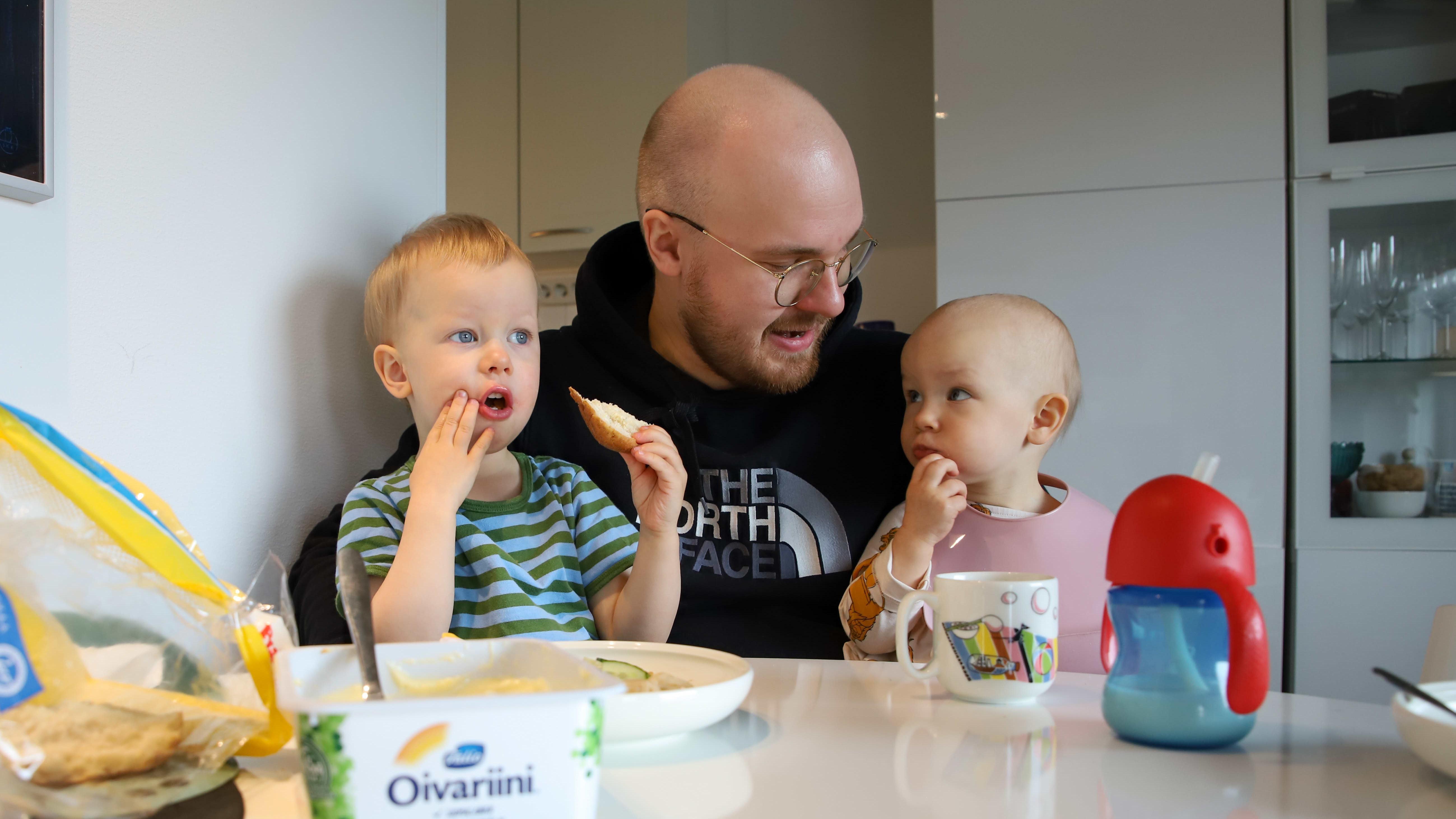Torniolainen Atte Tolonen istuu ruokapöydän ääressä lastensa Paulin ja Maikin kanssa. He syövät leipää.
