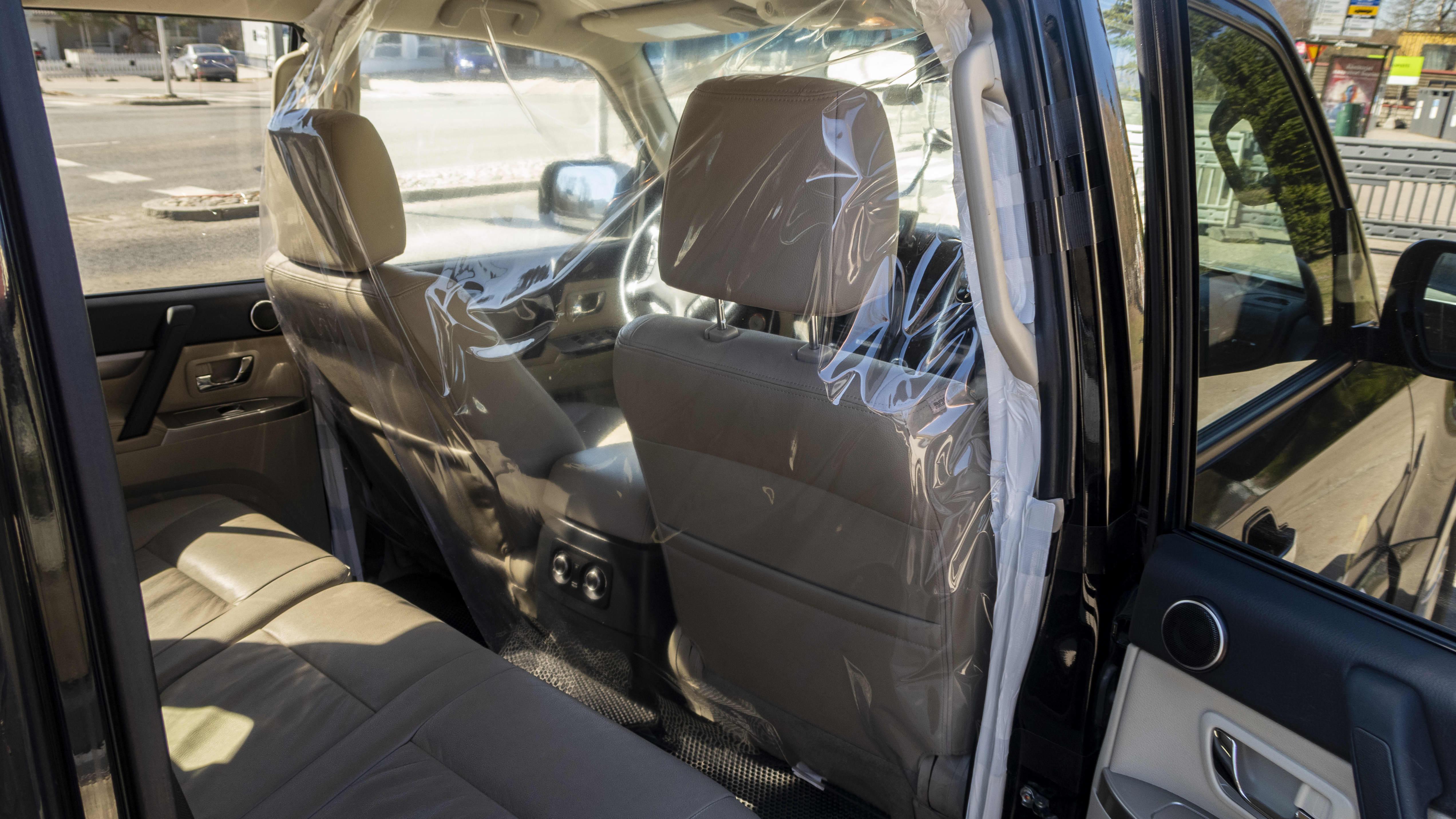 Koronaviruksen leviämistä vastaan asetettu suojamuovi taksissa