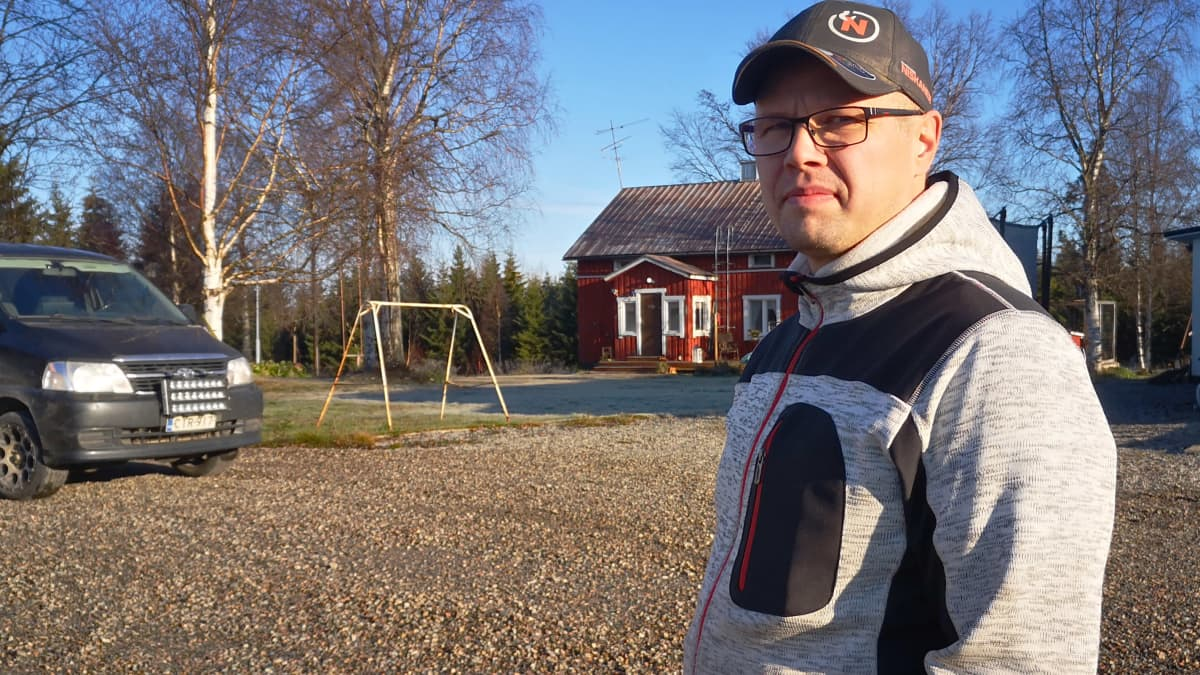 Kanalayrittäjä Janne Barsk seisoo pihassaan harmaassa takissa ja katsoo kameraan.