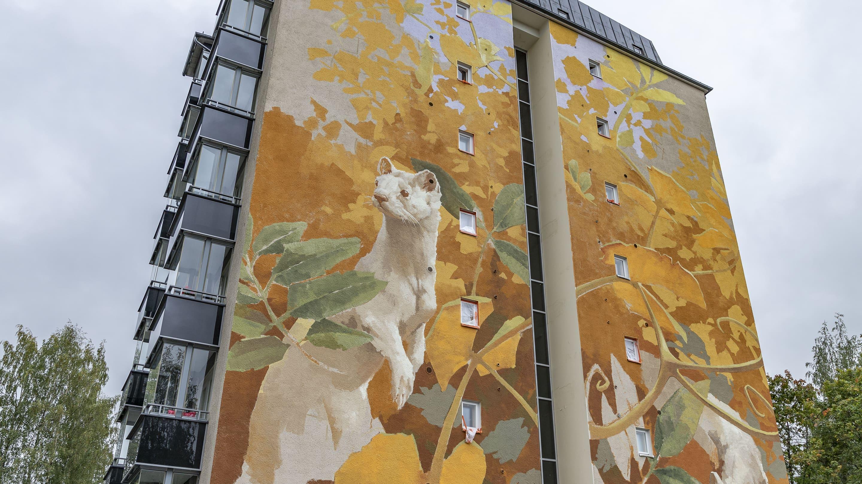 Kuva kerrostalon seinästä, jossa uusi seinämaalaus koreilee. Maalauksessa syksyisten kasvien lomasta kurkkii kaksi valkoista kärppää.