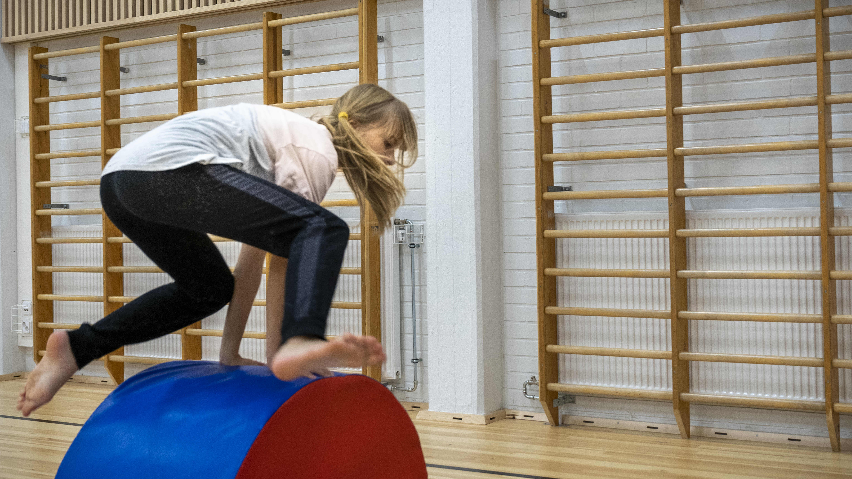 Tyttö tekee parkourtemppua koulun liikuntasalissa.
