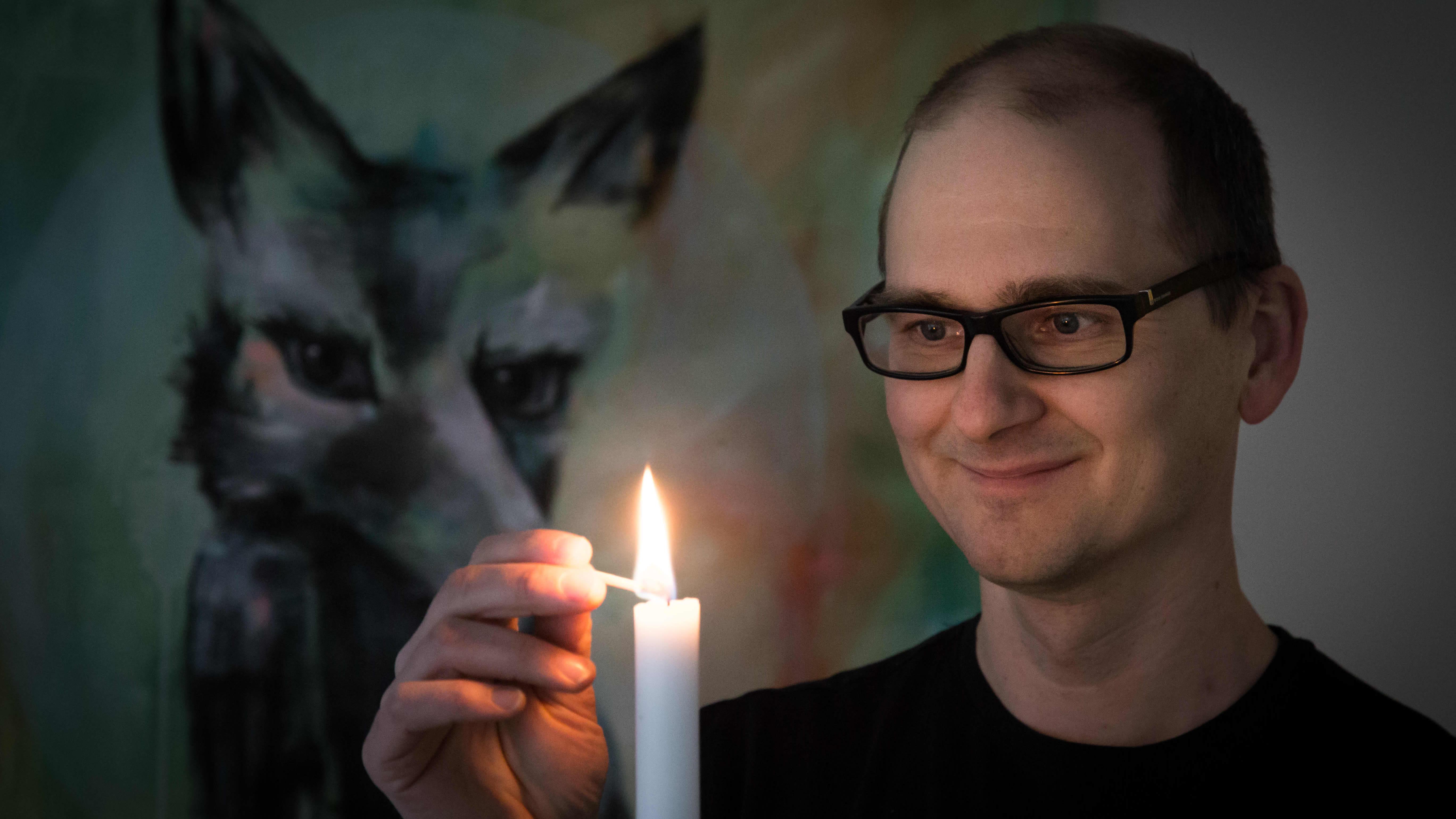 Leo Stranius sytyttää kynttilää.