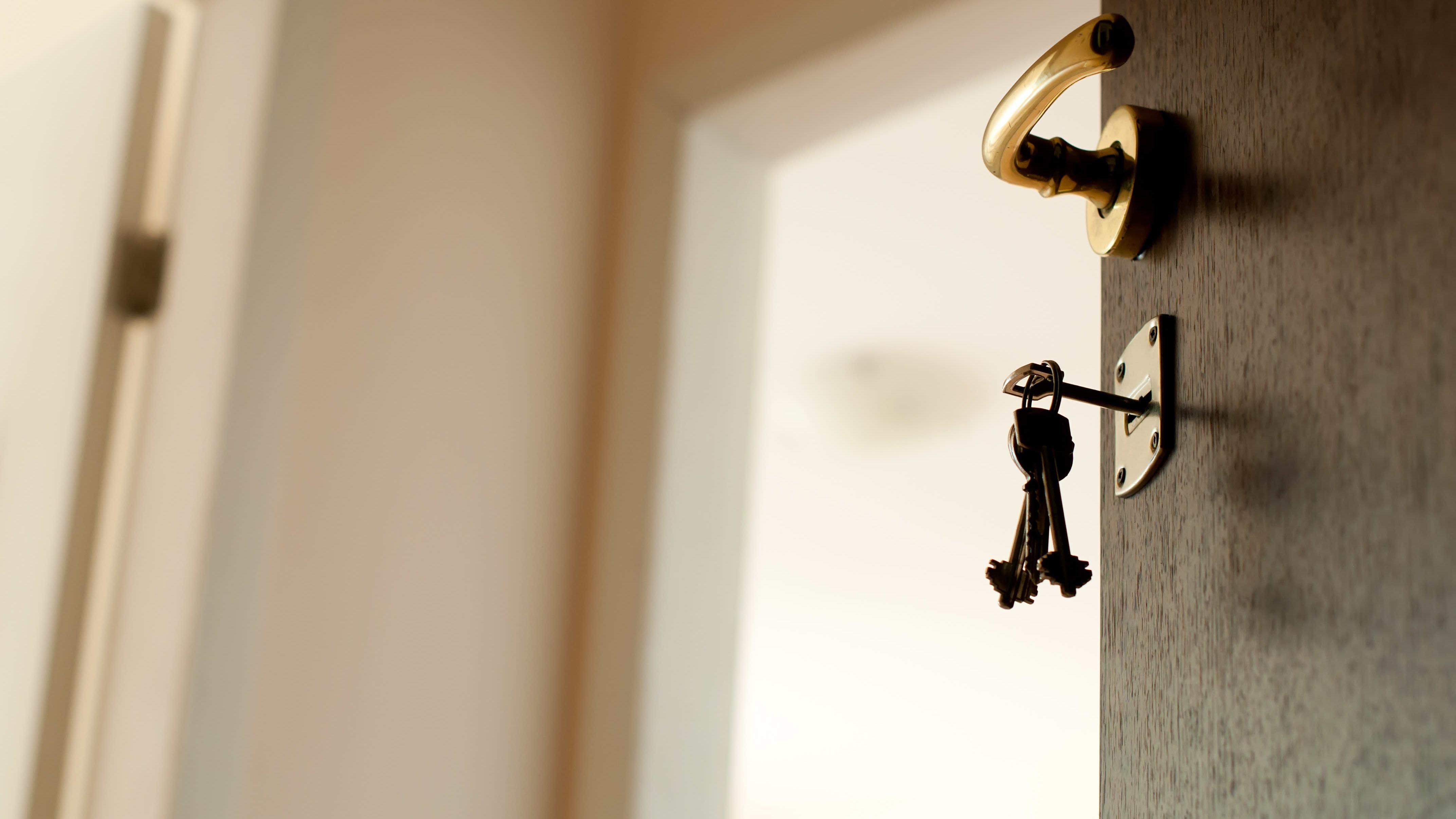 En nyckelknippe hänger i låset på en öppen dörr.