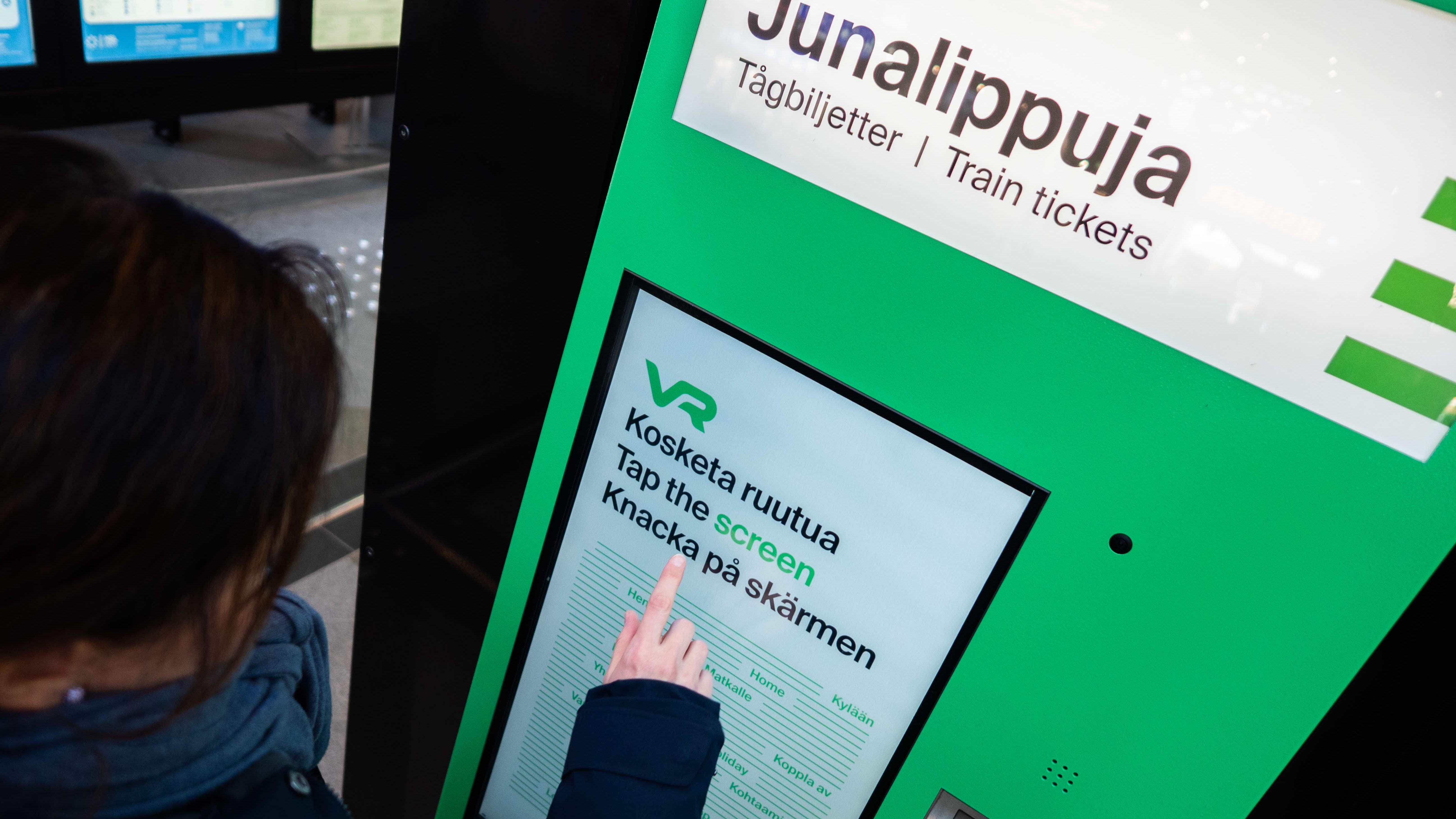 Nainen ostamassa VR:n lippuautomaatista lippua.