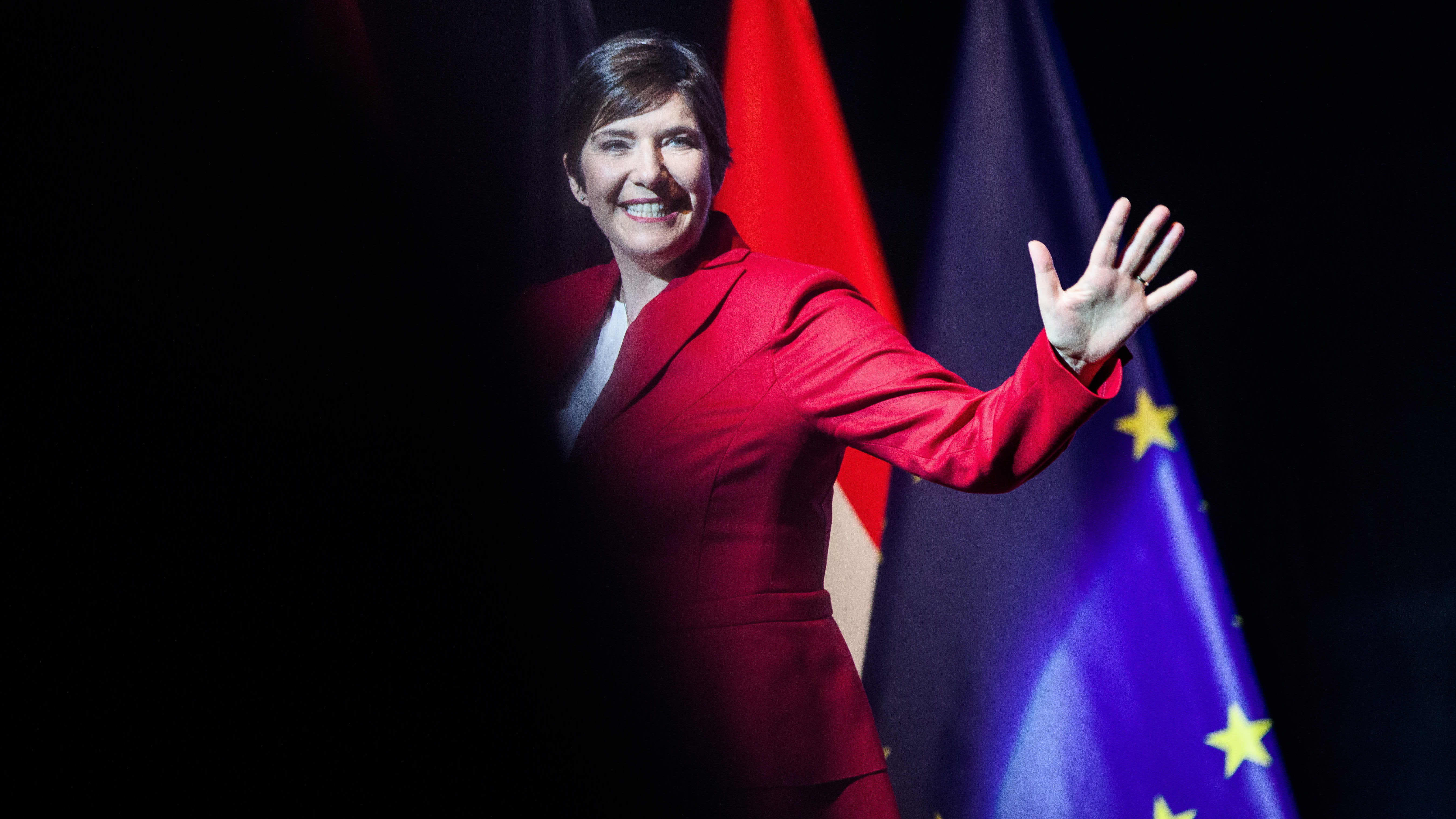 Klara Dobrev lavalla, hymyilee ja heiluttaa kättä.