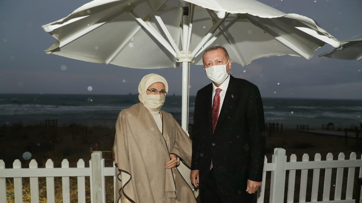 Turkin presidentti ja hänen vaimonsa seisovat sateessa auringonvarjon alla