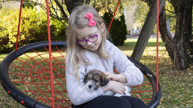 Emilia Campbell ja koira Charlie keinuvat kotipihallaan Tuusulassa