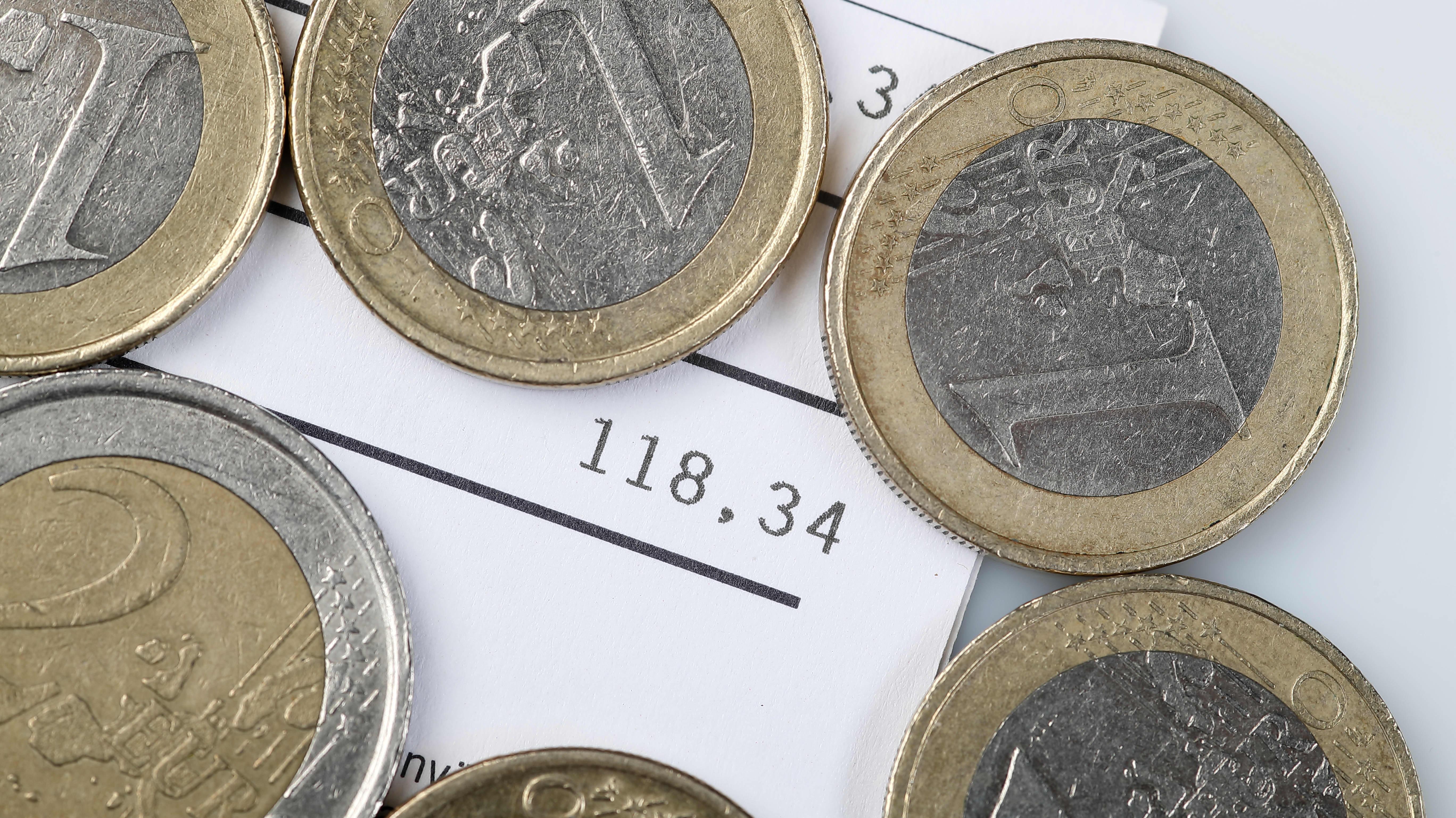 En hög med mynt ovanpå en räkning på 118 euro.