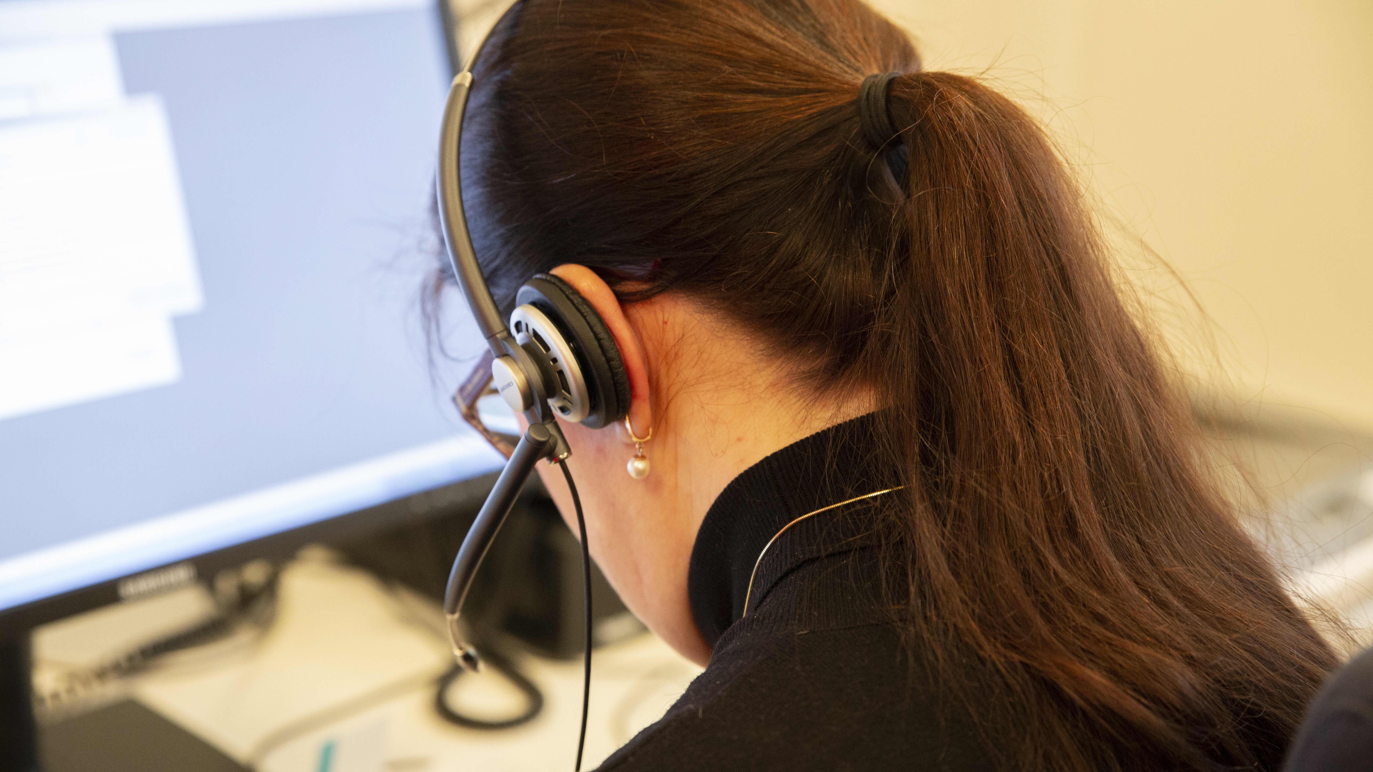 Nainen kuulokkeet korvillaan tietokoneen ääressä.