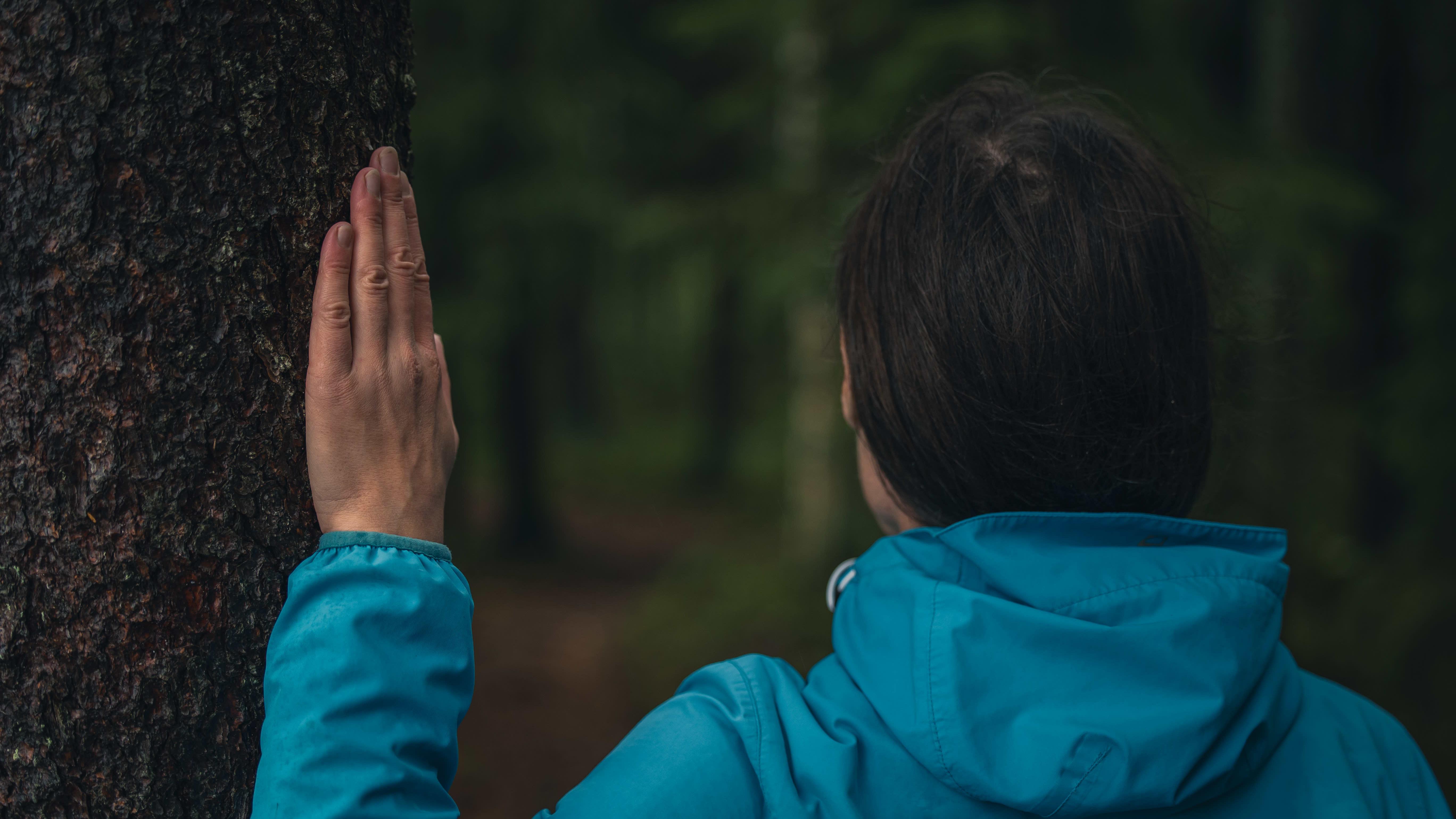 Nainen pitelee kättänsä puuta vasten.