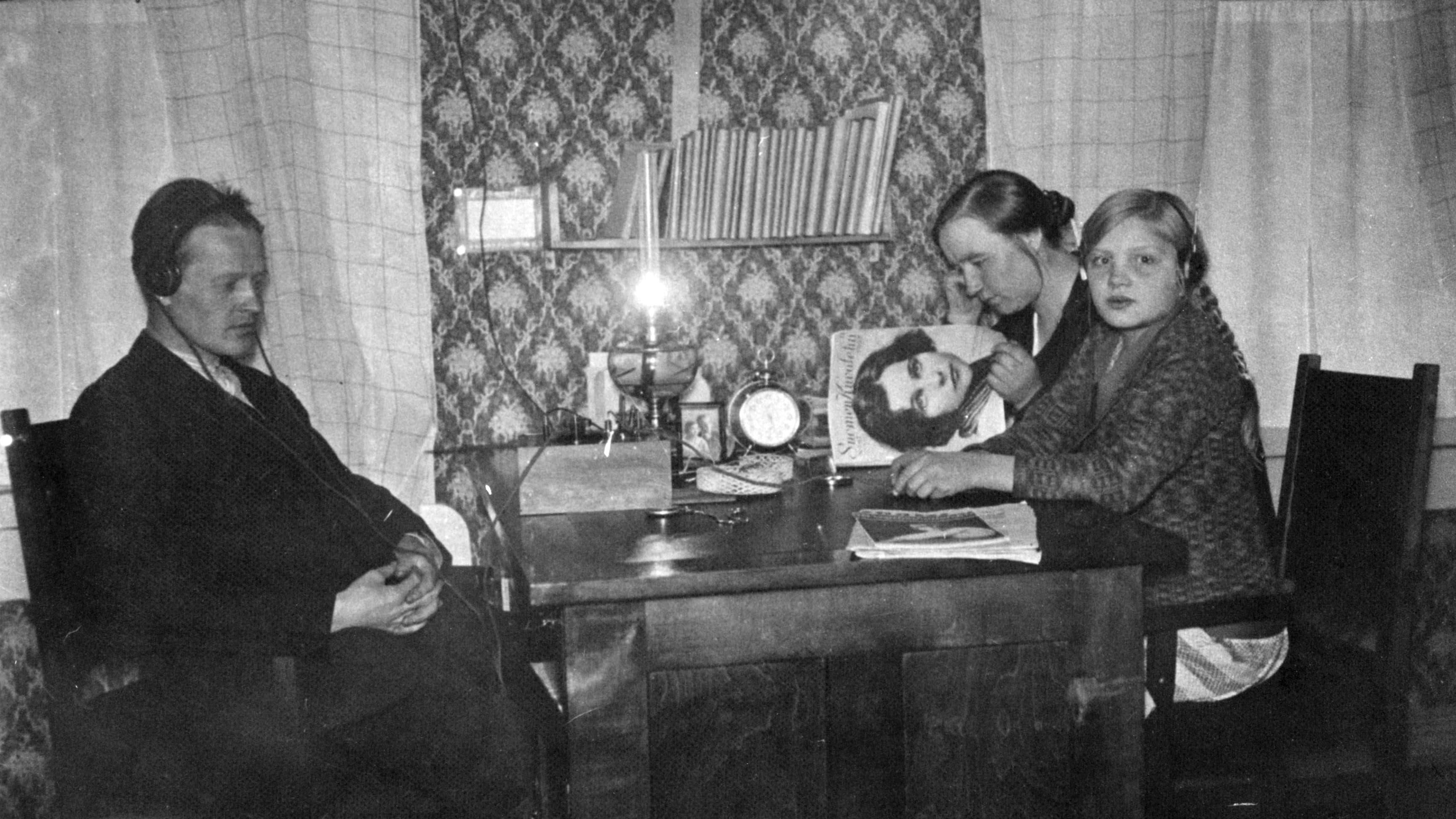 Lampaluodon ensimmäinen radio (kidekone). Radiota kuunnellaan saaristossa pöydän ääressä. Mies, tyttö ja lehteä lukeva nainen.