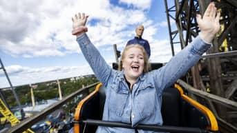 Nuori nainen on Linnanmäen vanhan vuoristoradan kyydissä kädet ylhäällä ja suuri hymy kasvoillaan. Taustalla näkyy jarrumies ja sinistä taivasta.