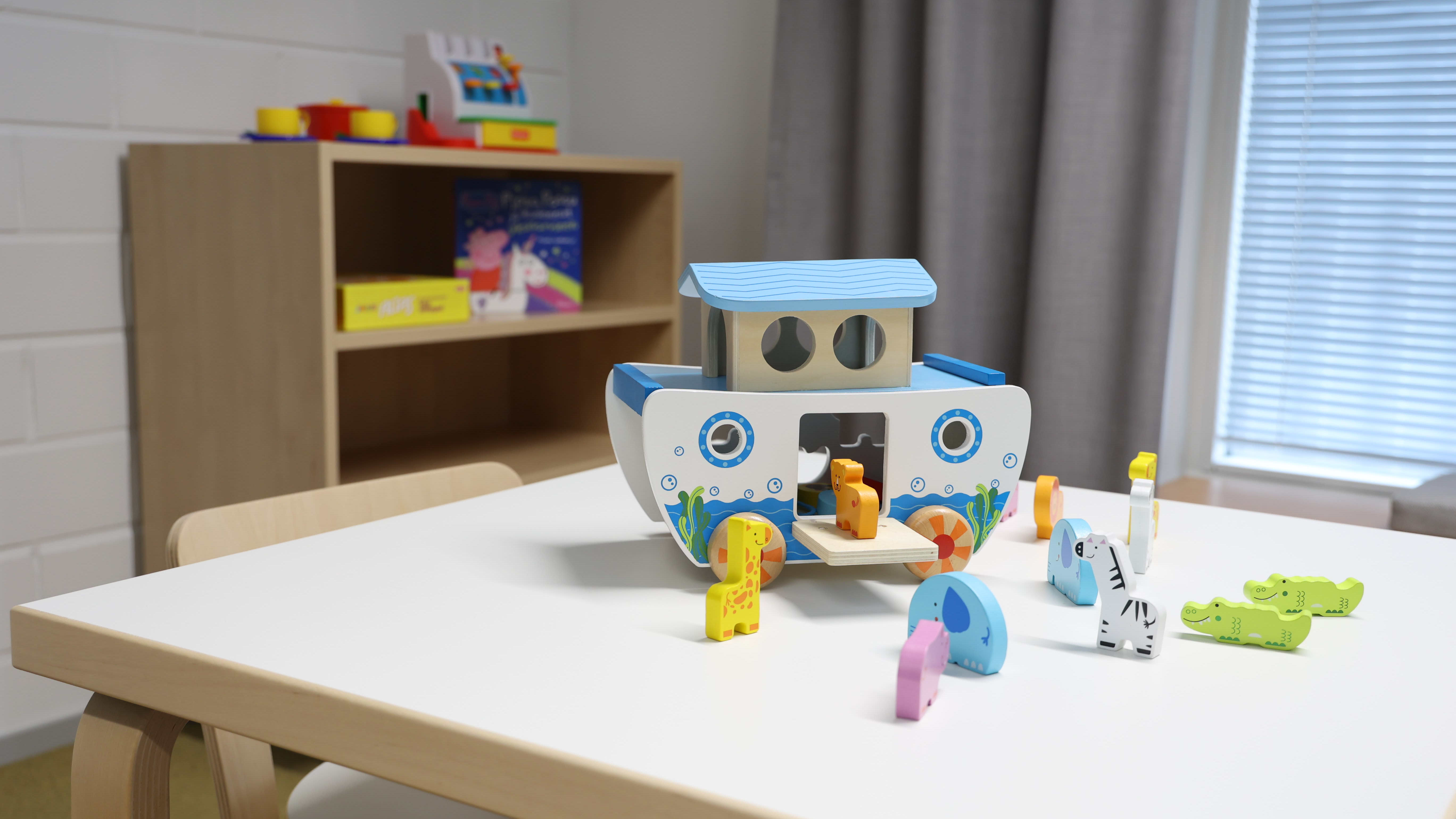Logopedian koulutusohjelman terapiahuoneessa on leluja pöydällä.