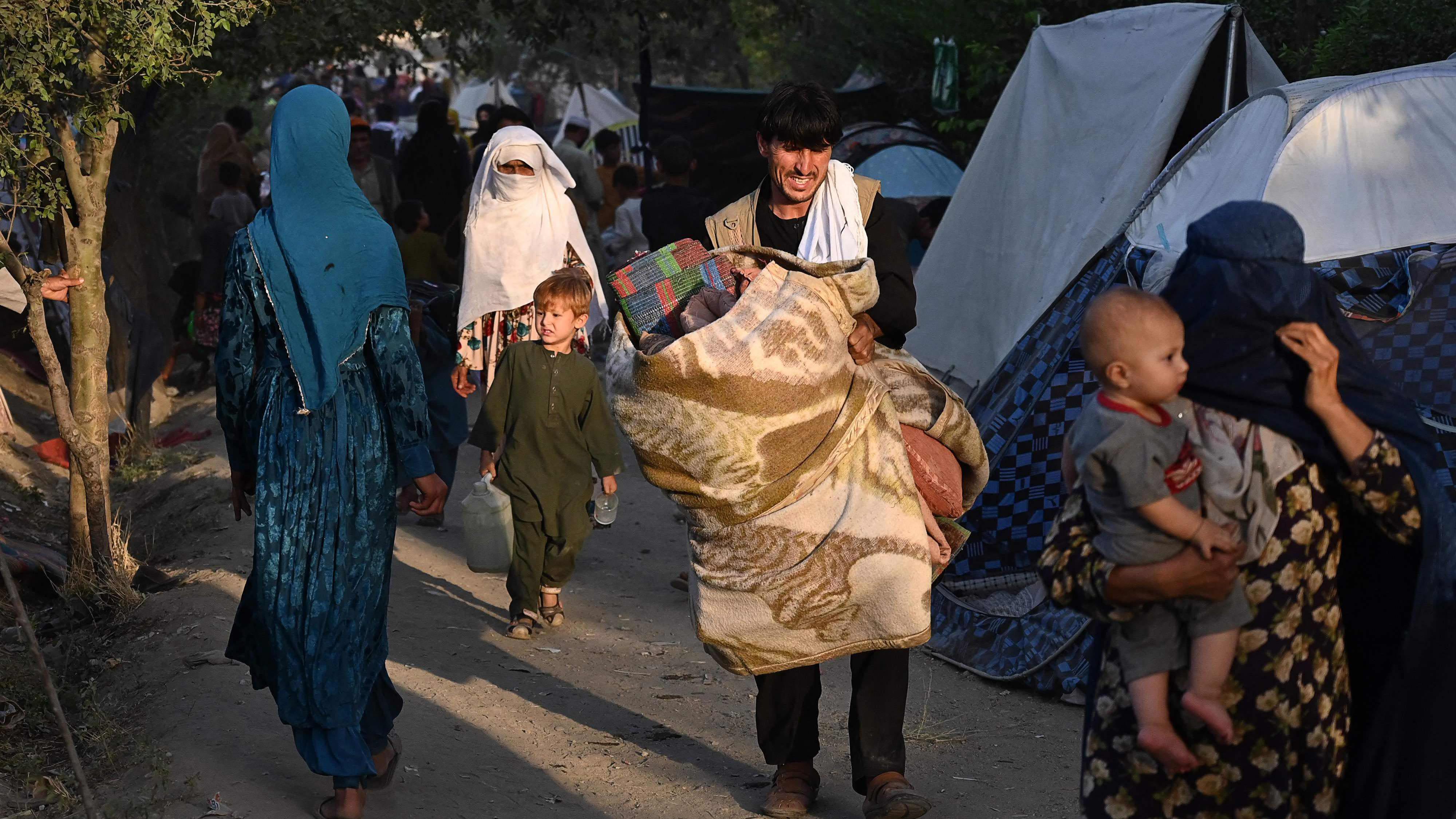 Ihmisiä, jotka ovat joutuneet pakenemaan kodeistaan, kävelemässä väliaikaisten telttamajoitusten ohi.