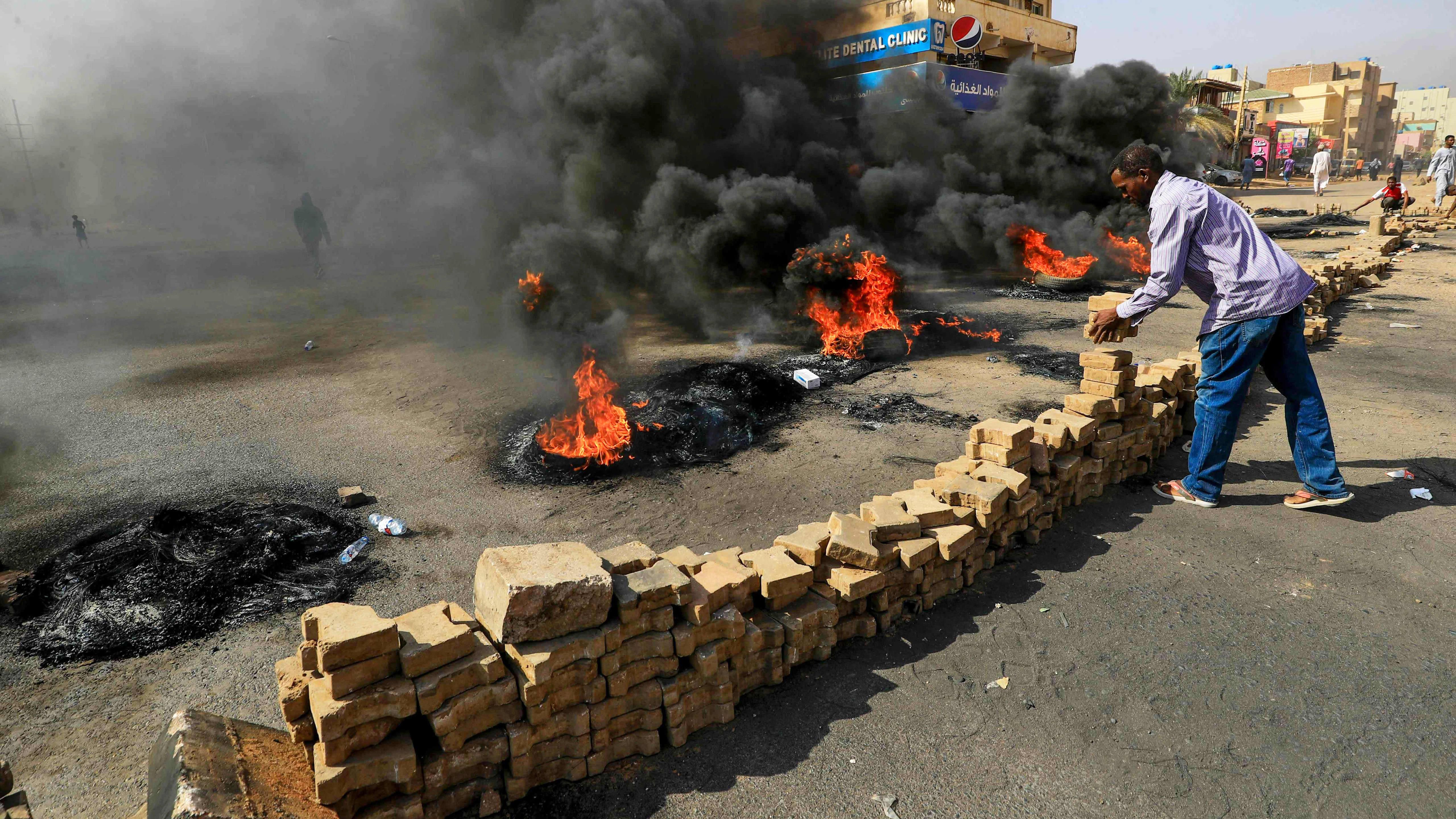 Mielenosoittajat polttavat autonrenkaita kadulla.