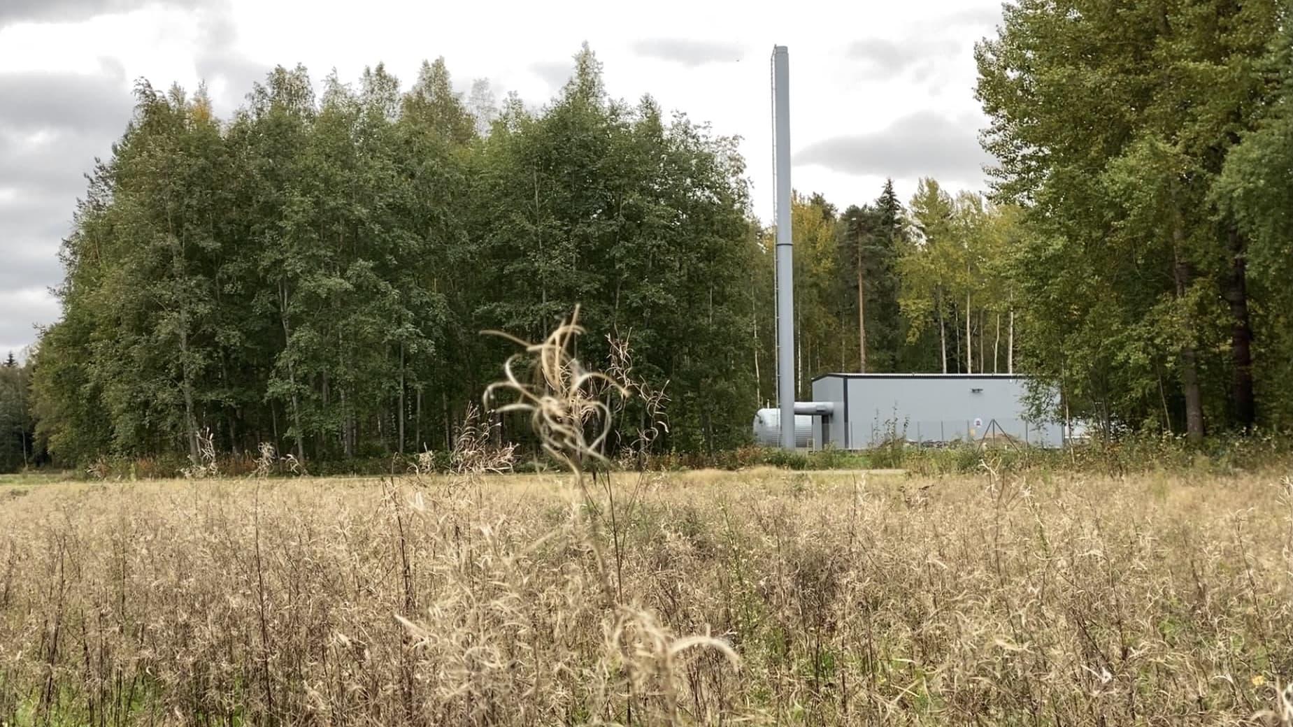 Pieni varalämpövoimala. Edessä niittyä, voimalan ympärillä metsää.