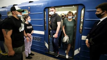 Kasvomaskeihin pukeutuneita matkustajia Pietarin metrossa.