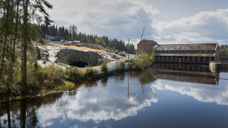 Kallioon, Kuhankakosken vanhan voimalaitoksen viereen, on räjäytetty tunneli rakenteilla olevan voimalaitoksen käyttöön. Pilvet heijastuvat taivaalta veteen.