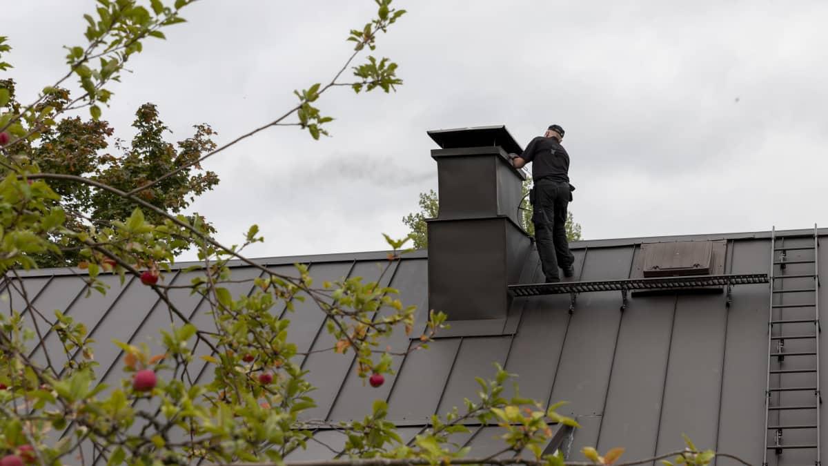 Nuohooja puhdistaa talon katolla savupiippua