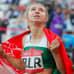 Krystsina Tsimanouskaja kääriytyneenä Valko-Venäjän lippuun.
