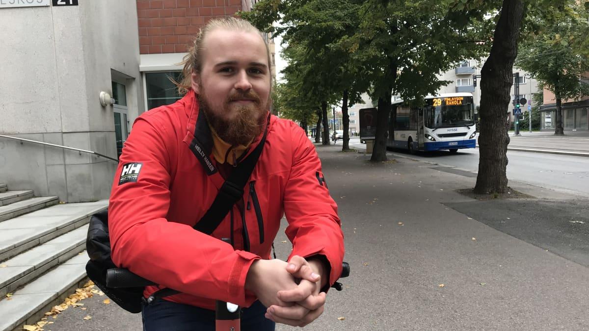 Opiskelija Kalle Torikka nojaa sähköpotkulautaan.