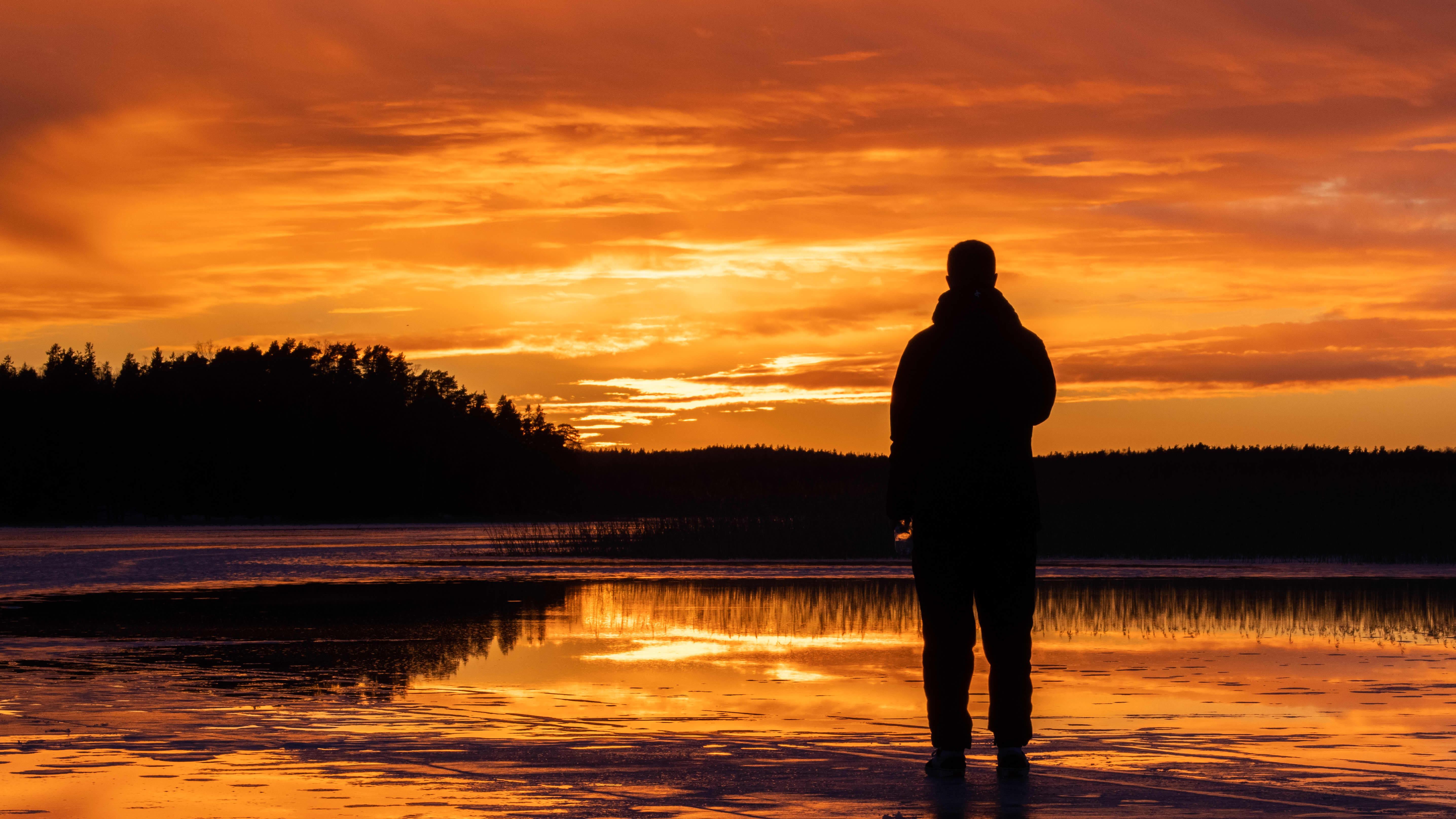 Henkilö meren jäällä katsoo auringonlaskua.