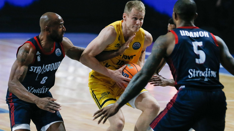 Sasu Salin koripallo kädessä, kahden vastustajan välissä.