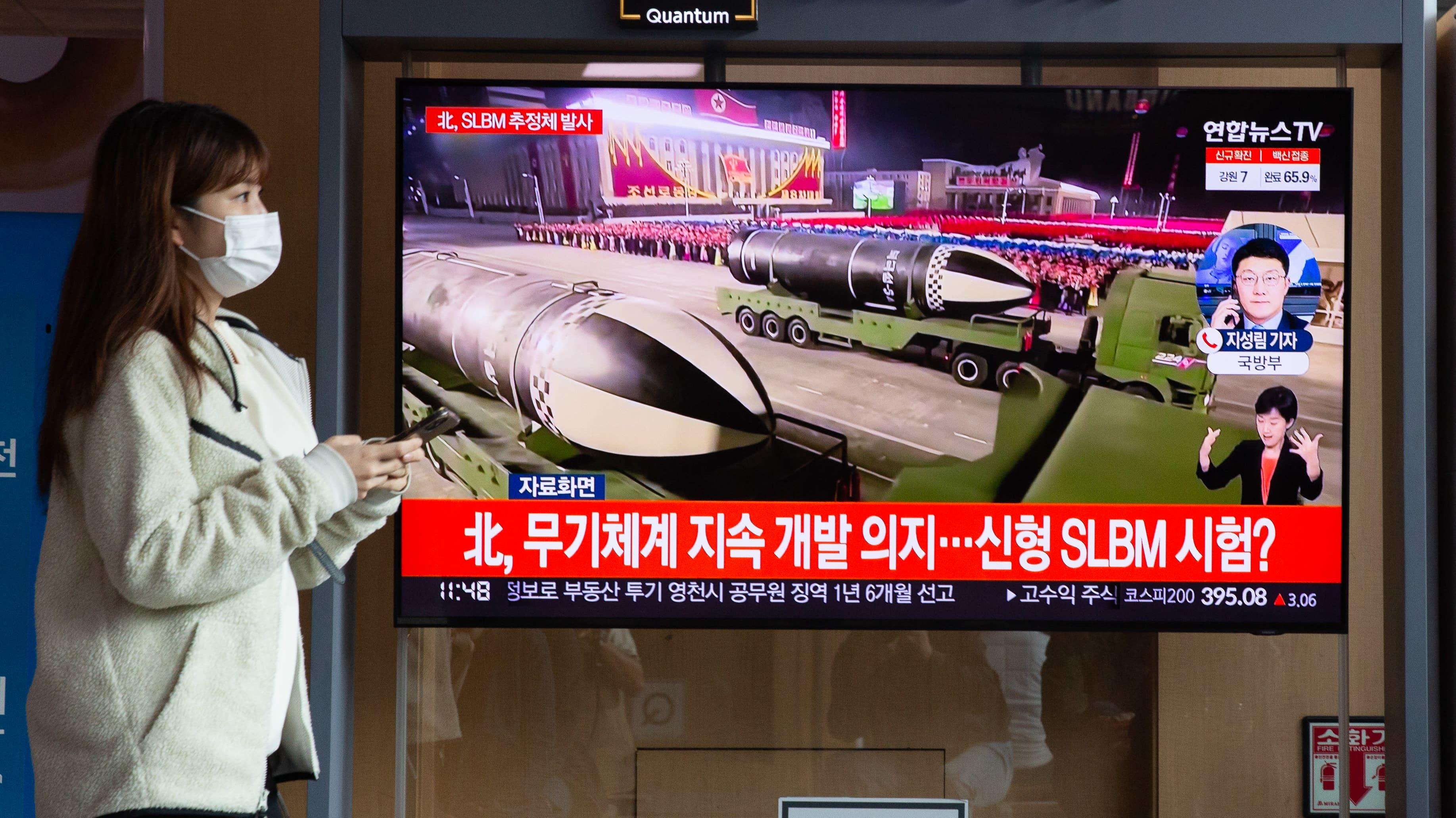 Nainen kulki televisioruudun ohi asemalla Etelä-Korean pääkaupungissa Soulissa. Uutisissa kerrotaan Pohjois-Korean juuri laukaisemasta ohjuksesta.