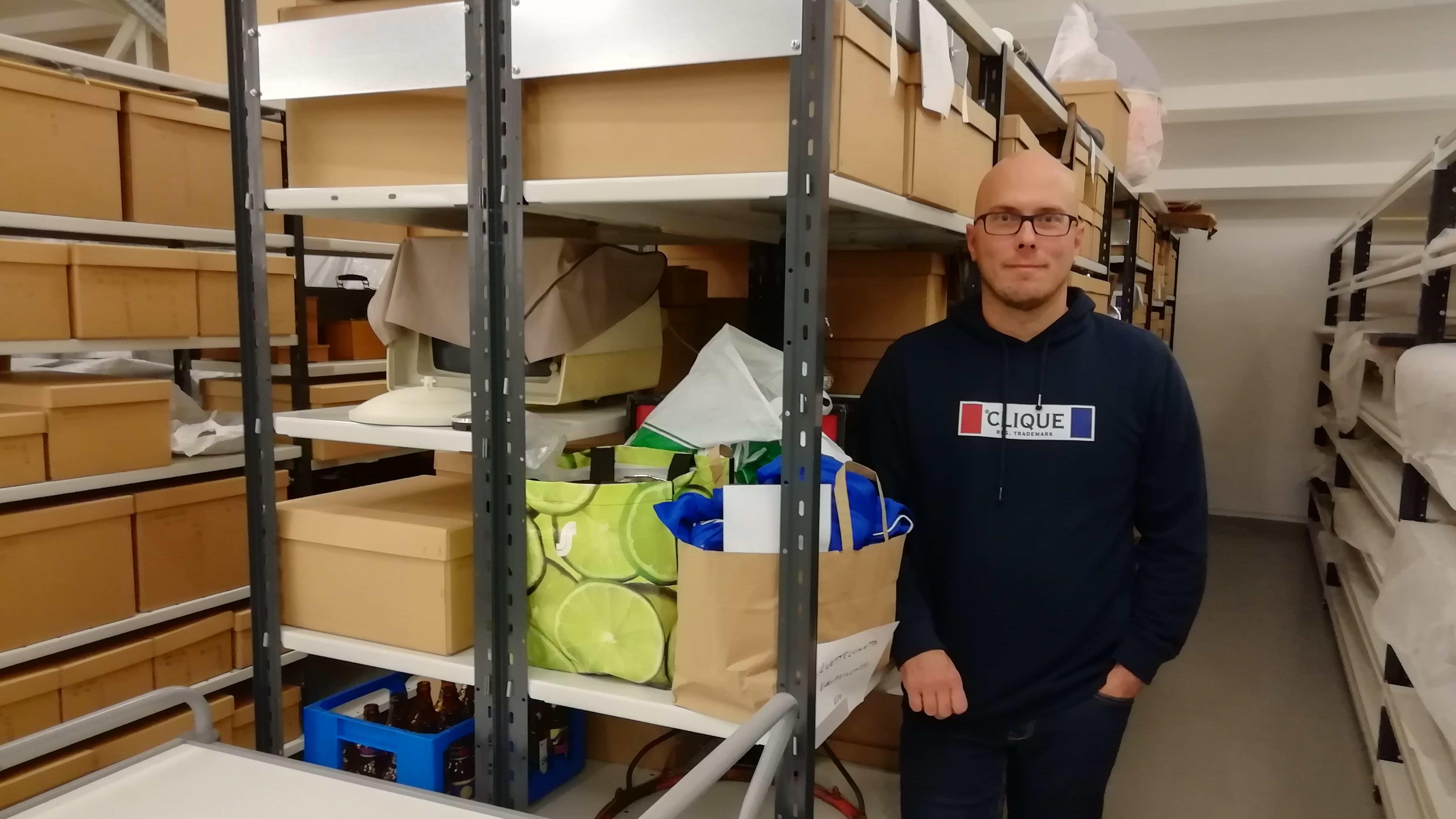 Koripallomuseon kokoelmia varastossa, toiminnanjohtaja Jari Toivonen seisomassa käytävällä